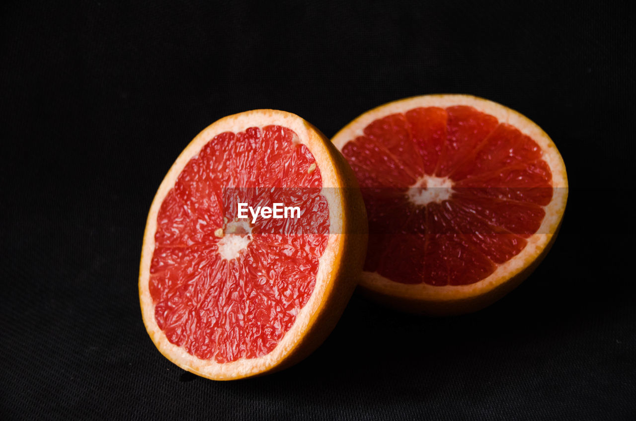 fruit, healthy eating, studio shot, food and drink, food, wellbeing, freshness, indoors, black background, cross section, close-up, slice, no people, still life, red, halved, citrus fruit, orange color, cut out, group of objects, ripe, orange