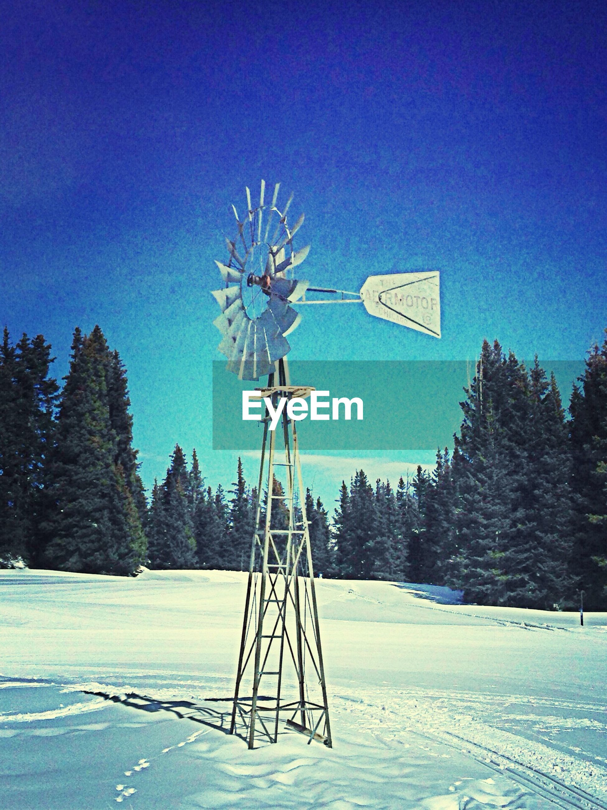 Traditional windmill on snow covered field by trees against clear blue sky
