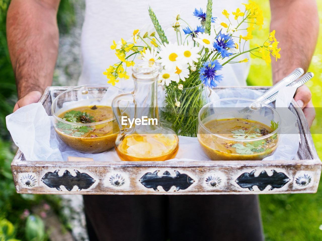 Close-Up Of Young Man Offering Food Tray With Flowers