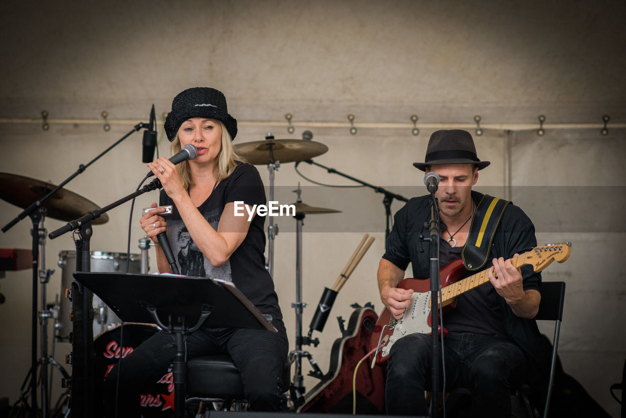 playing, music, musical instrument, performance, musician, drum kit, performance group, singing, real people, event, arts culture and entertainment, singer, young men, drummer, recording studio, young adult, electric guitar, indoors, guitar, day, people