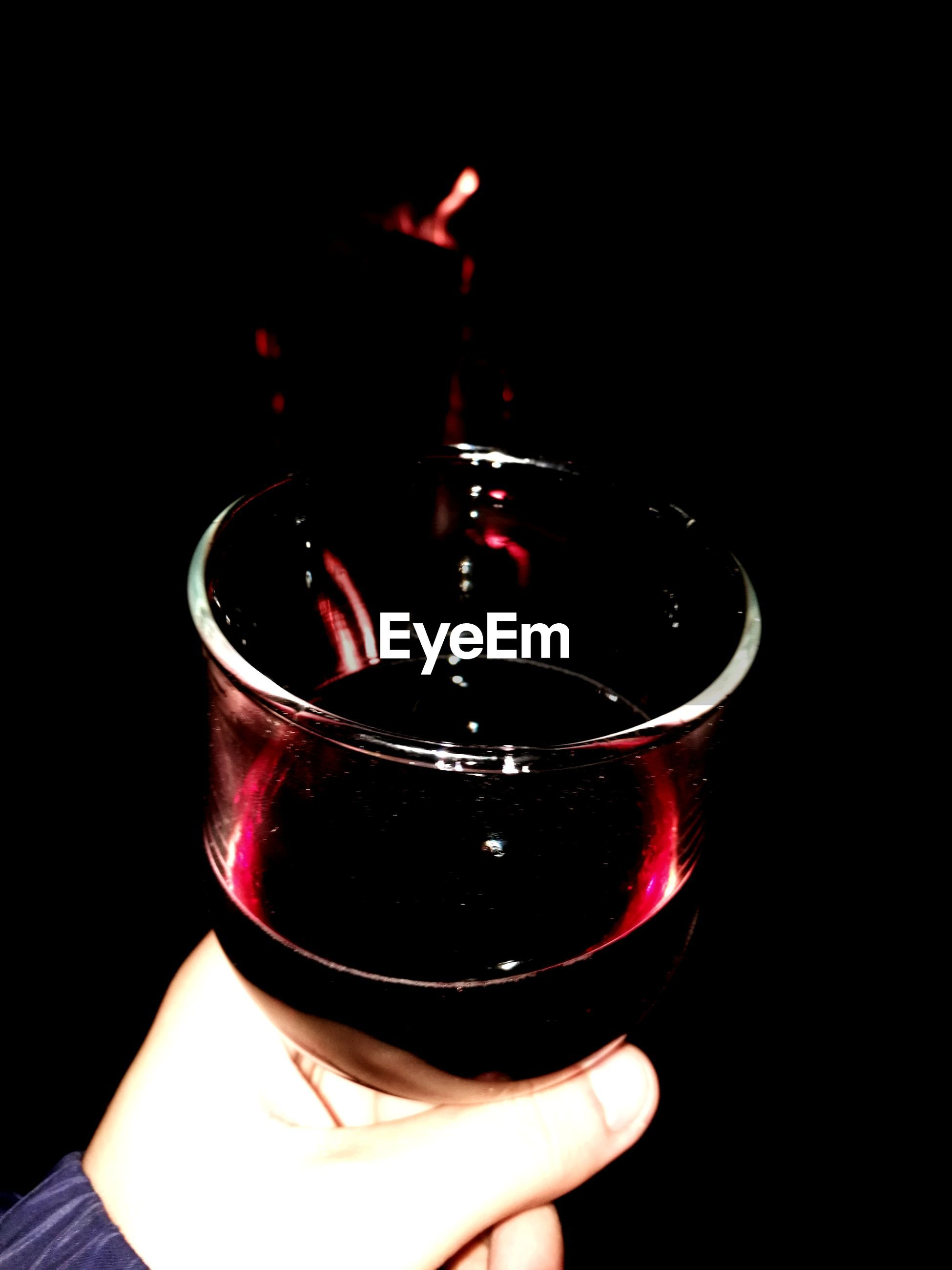 drink, human hand, black background, refreshment, alcohol, food and drink, real people, holding, one person, flame, close-up, night, heat - temperature, burning, human body part, wine, wineglass, drinking glass, indoors, illuminated, freshness
