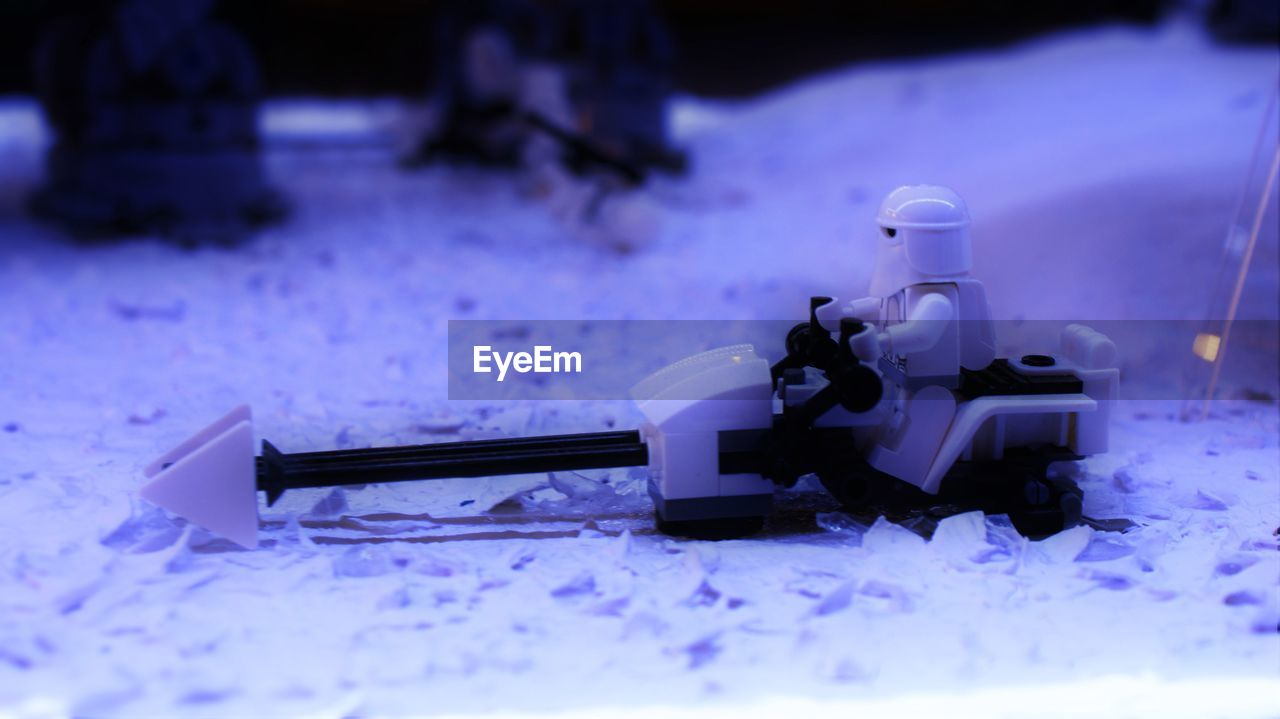 figurine, selective focus, snow, no people, weapon, night, winter, indoors, close-up