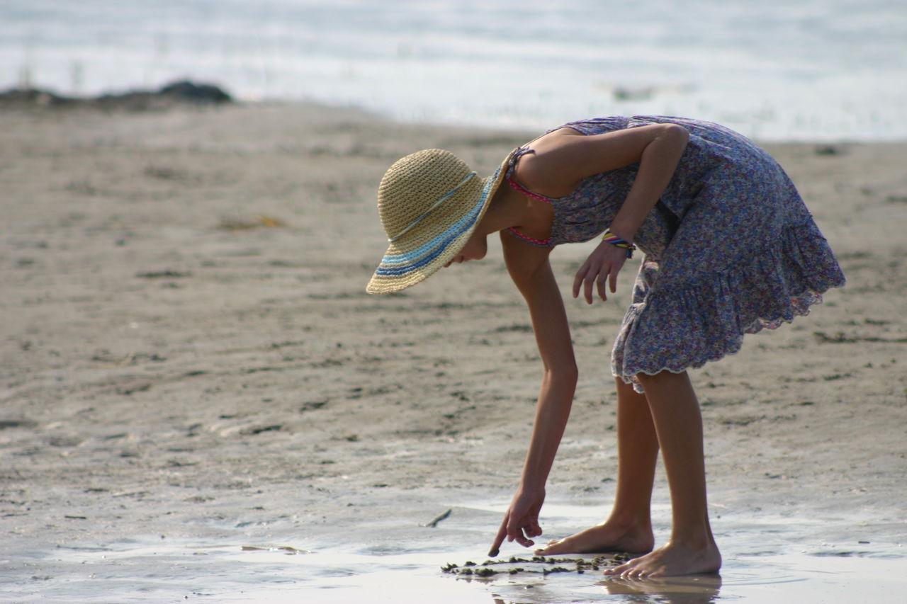 Girl Drawing On Sand On Beach