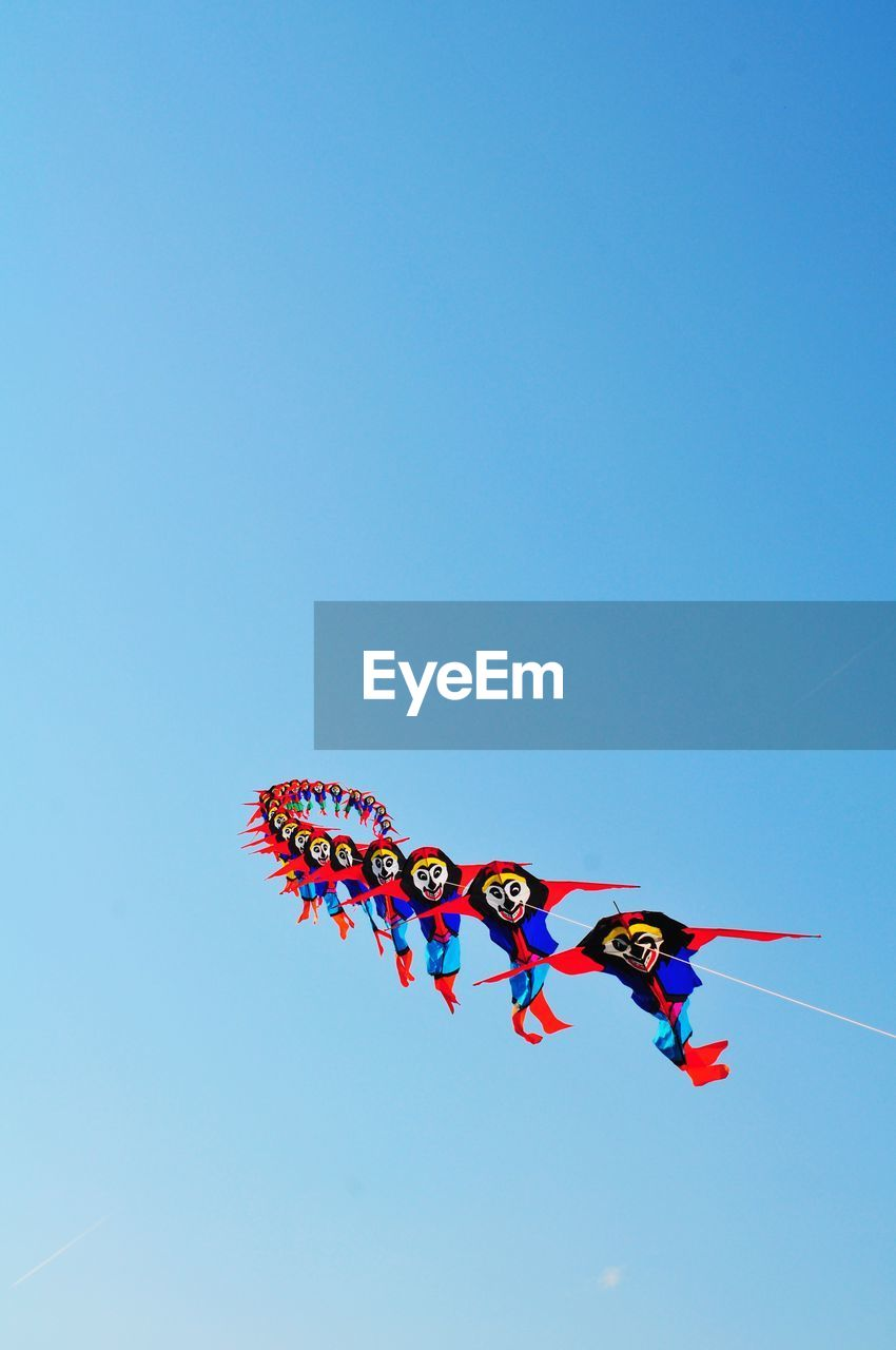 sky, multi colored, low angle view, clear sky, copy space, flying, blue, representation, nature, no people, animal representation, celebration, art and craft, creativity, day, mid-air, decoration, outdoors, kite, wind