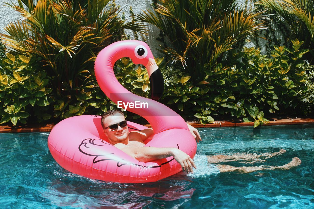 Full Length Of Happy Shirtless Man Relaxing On Flamingo Shape Inflatable Ring In Pool
