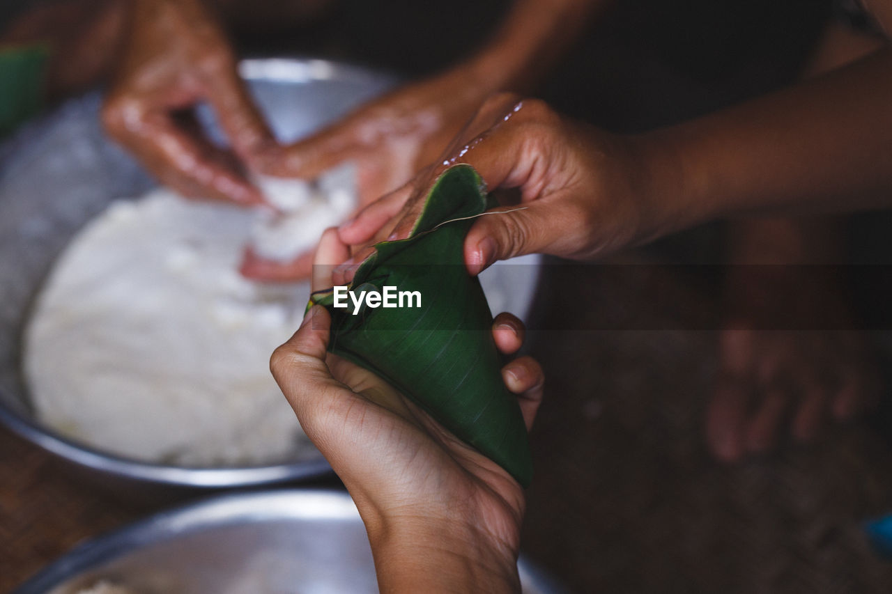 High Angle View Of Woman Wrapping Rice Cakes In Banana Leaf Cone