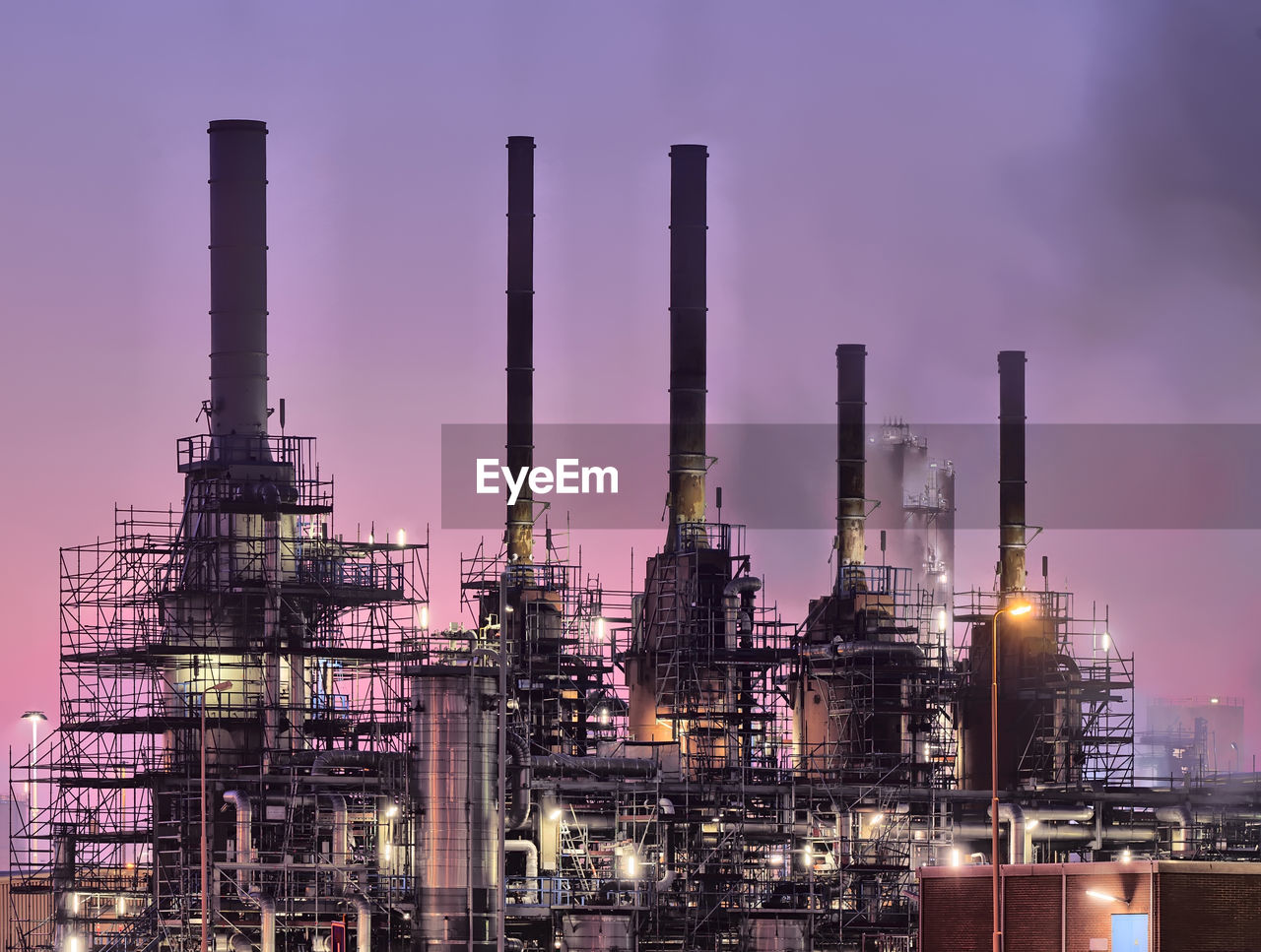 Low angle view of chemical plant against purple sky