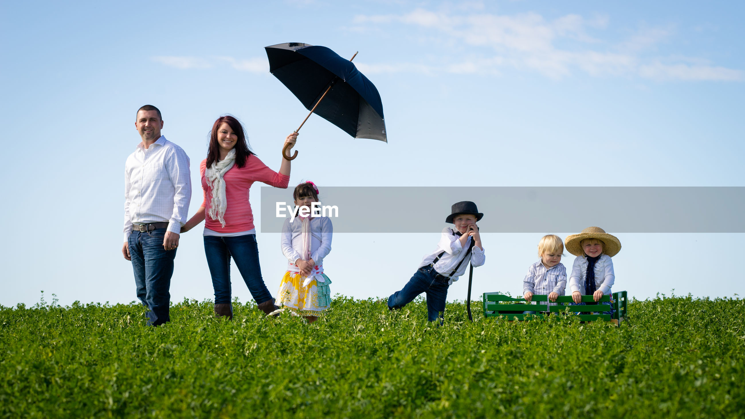 Portrait of family standing amidst plants against sky