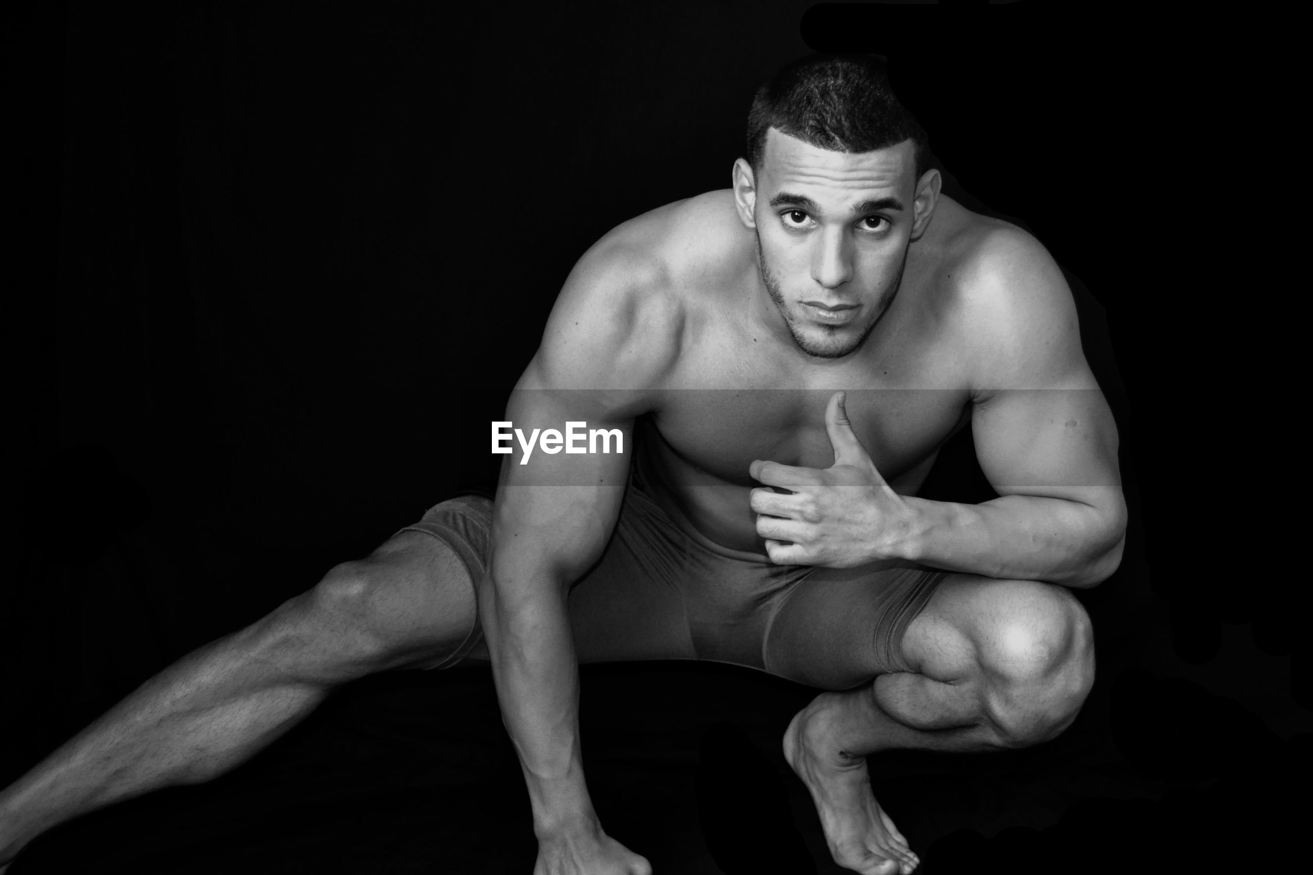 Portrait of young muscular man exercising against black background