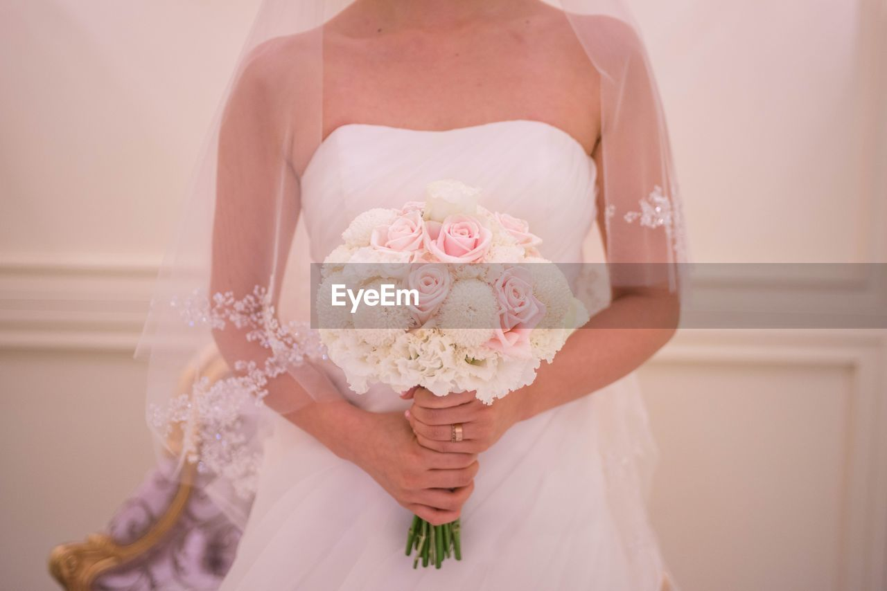 flower, flowering plant, plant, midsection, wedding dress, celebration, holding, one person, real people, front view, women, wedding, event, bride, life events, adult, newlywed, freshness, flower arrangement, lifestyles, bouquet, wedding ceremony, couple - relationship, flower head