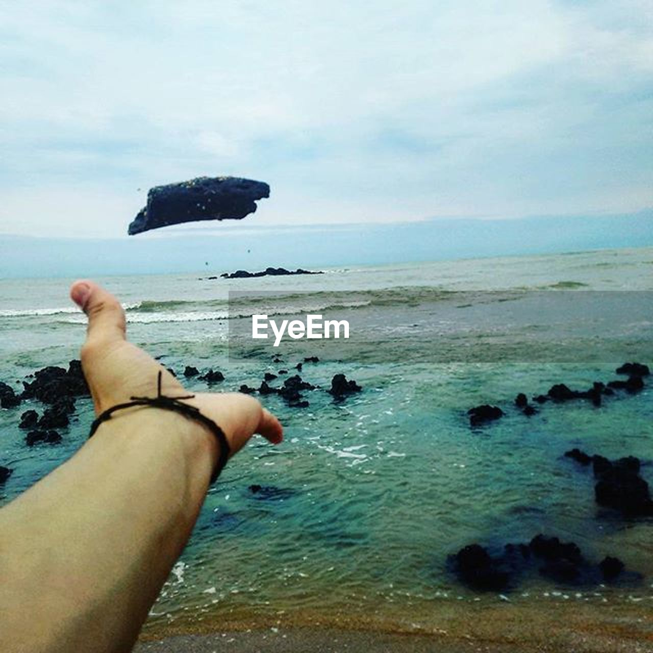 sea, human hand, water, hand, sky, human body part, one person, real people, horizon over water, beach, horizon, land, nature, day, beauty in nature, personal perspective, holding, scenics - nature, lifestyles, body part, outdoors, finger