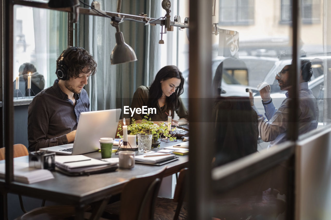 table, wireless technology, business, sitting, communication, adult, laptop, technology, food and drink, computer, connection, using laptop, women, restaurant, young adult, young women, indoors, working, mid adult, men