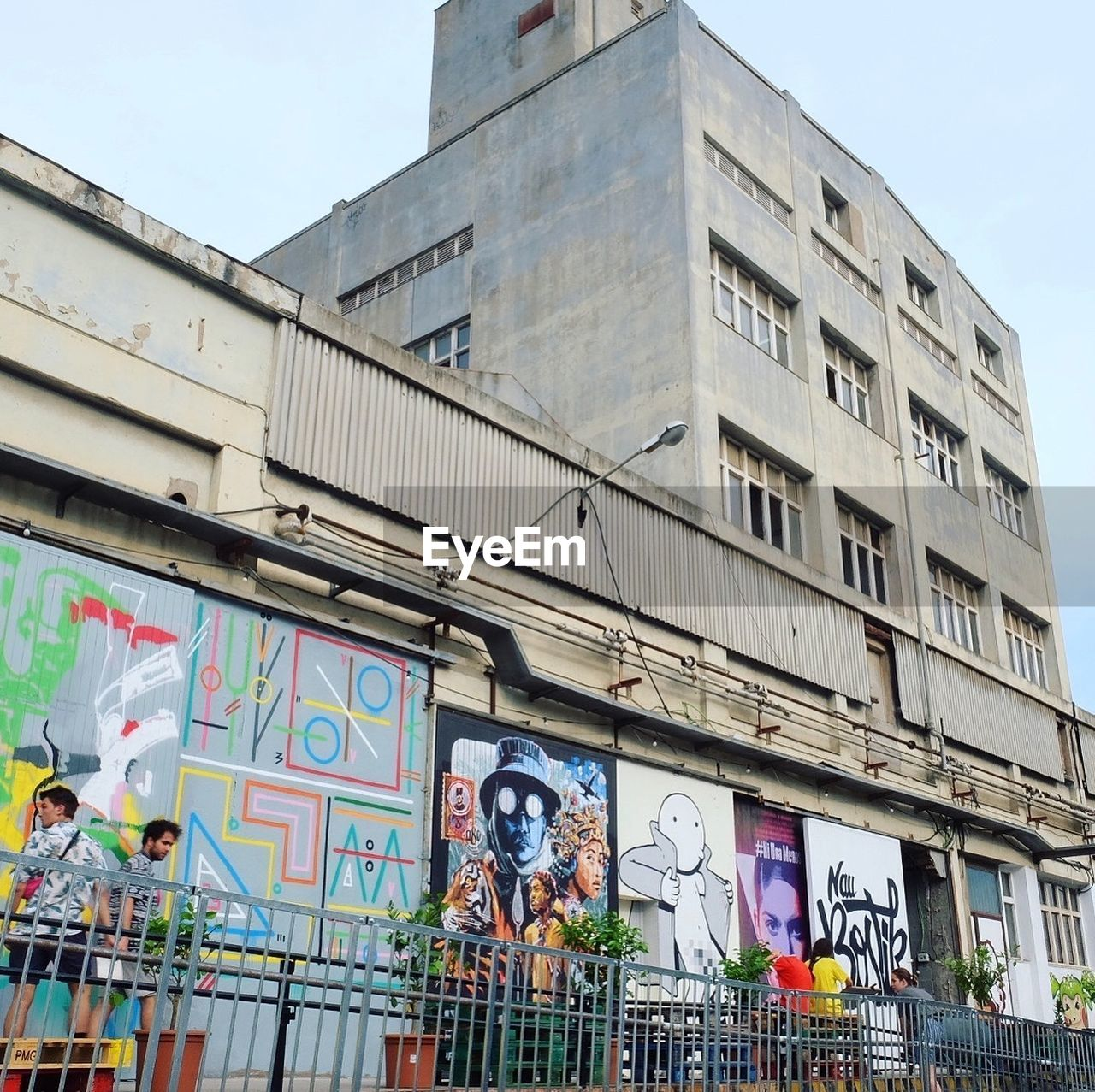 architecture, text, building exterior, built structure, graffiti, human representation, day, outdoors, low angle view, no people, city, sky
