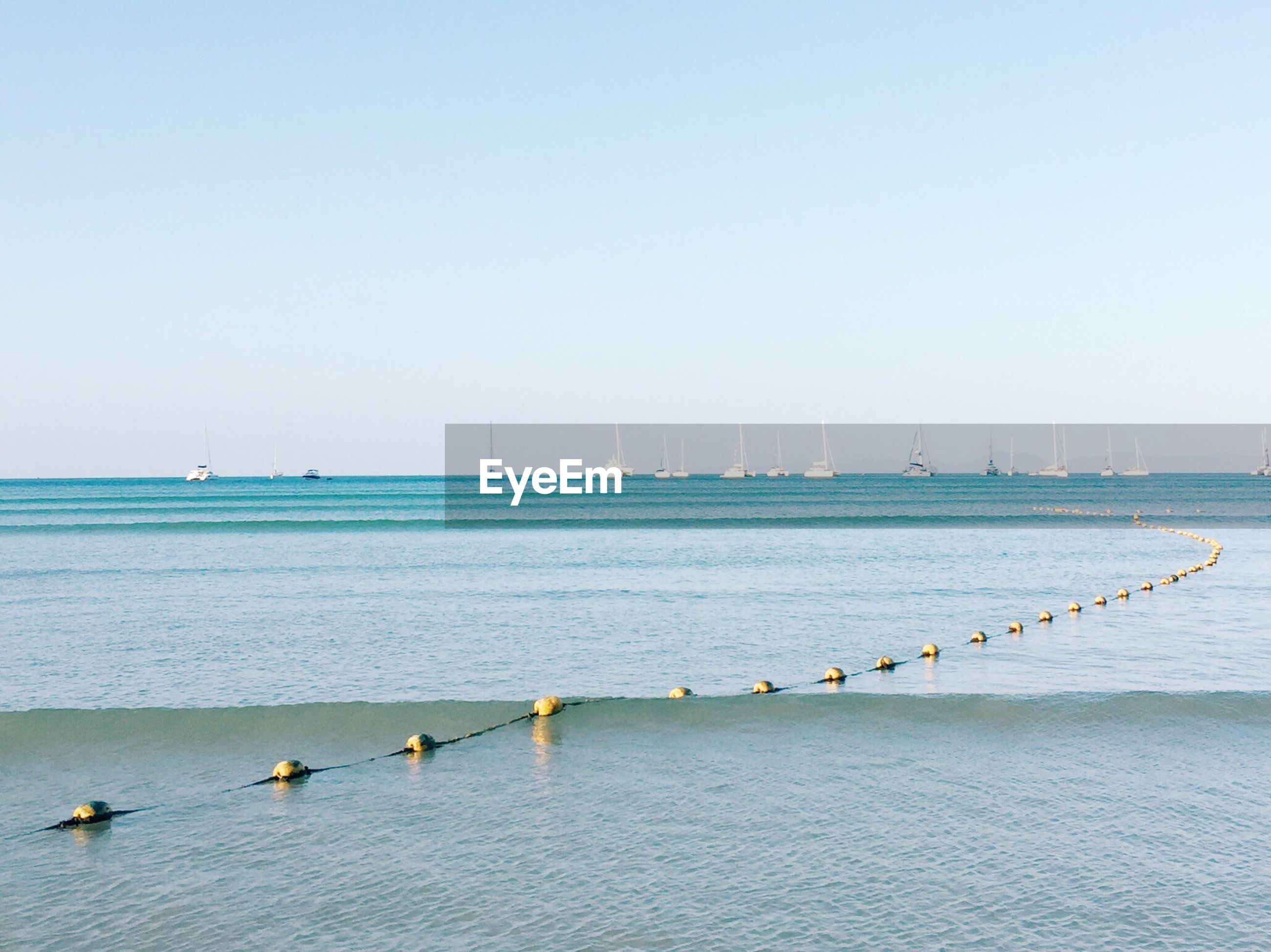 Buoys attached to rope floating in sea