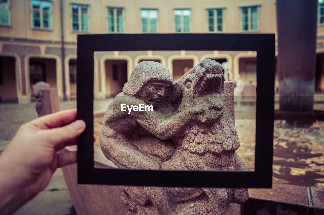 Close-up of person hand taking picture of statue with tablet