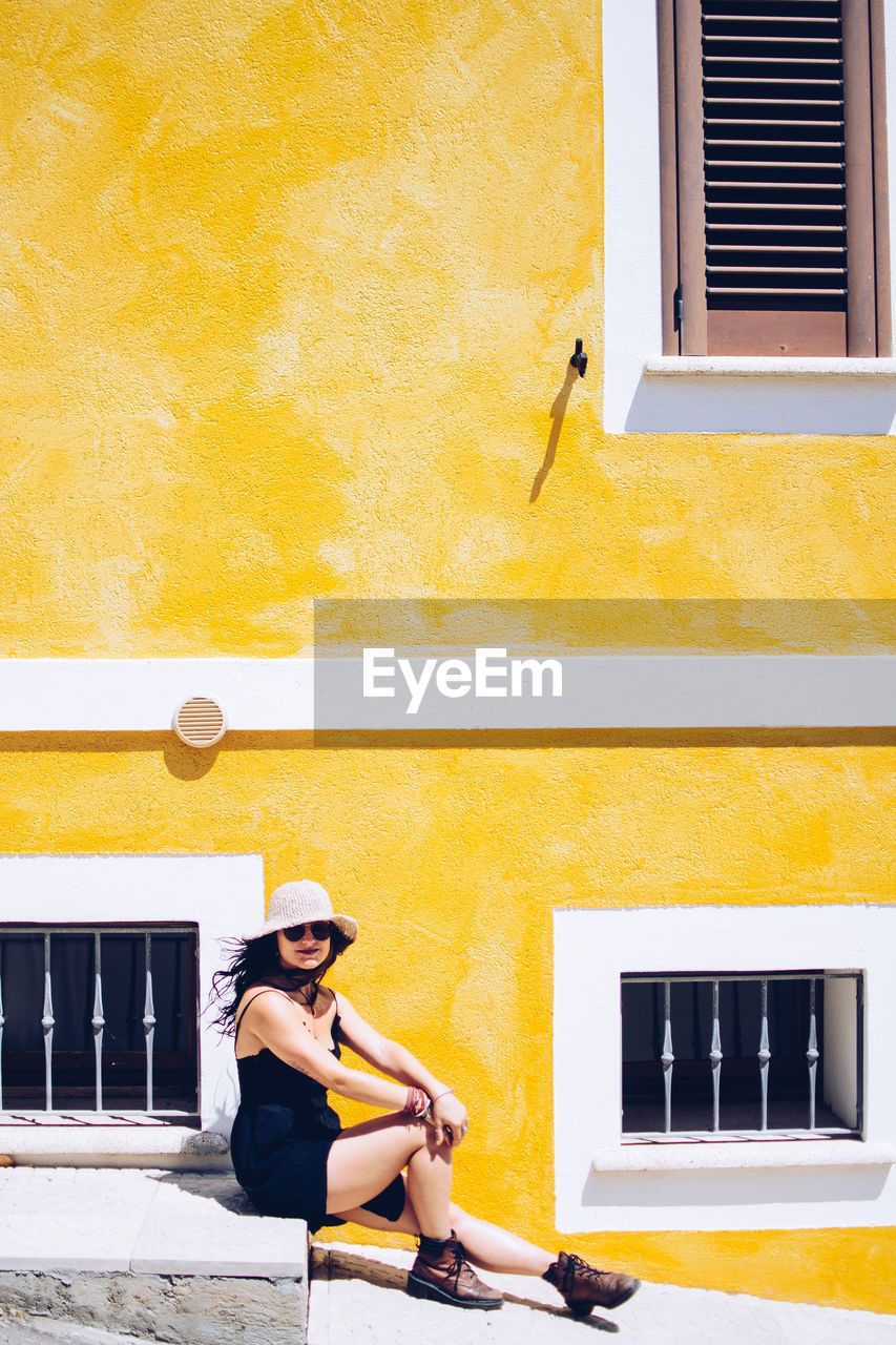 Young Woman Sitting Against Yellow Building During Sunny Day