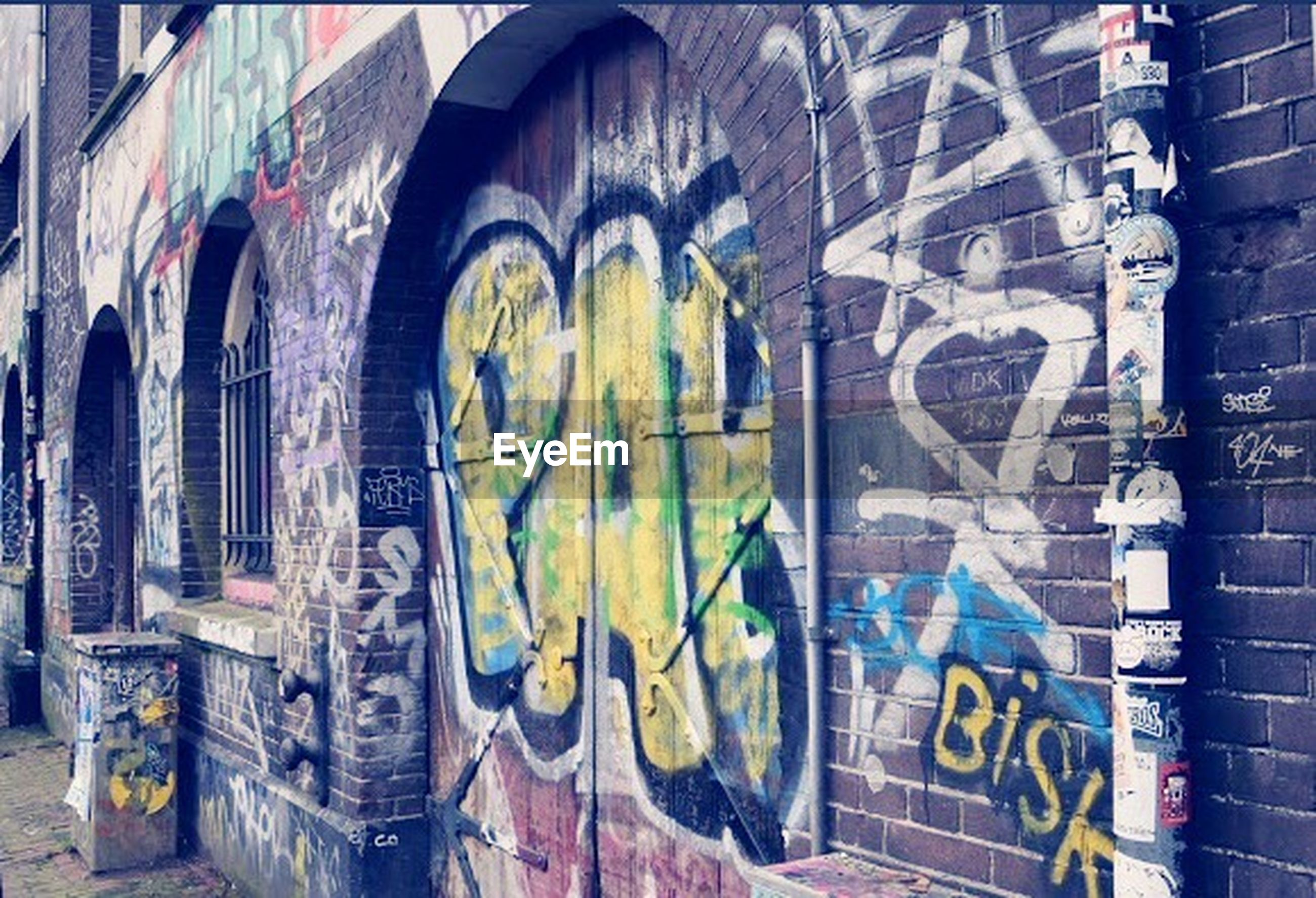 architecture, graffiti, built structure, building exterior, art and craft, art, creativity, wall - building feature, text, street art, arch, window, building, human representation, multi colored, day, wall, brick wall, mural, no people