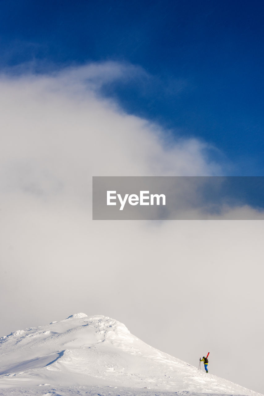 sky, cold temperature, winter, scenics - nature, beauty in nature, snow, mountain, cloud - sky, tranquility, tranquil scene, nature, day, one person, leisure activity, real people, lifestyles, unrecognizable person, non-urban scene, environment, snowcapped mountain, mountain range, outdoors, warm clothing, mountain peak