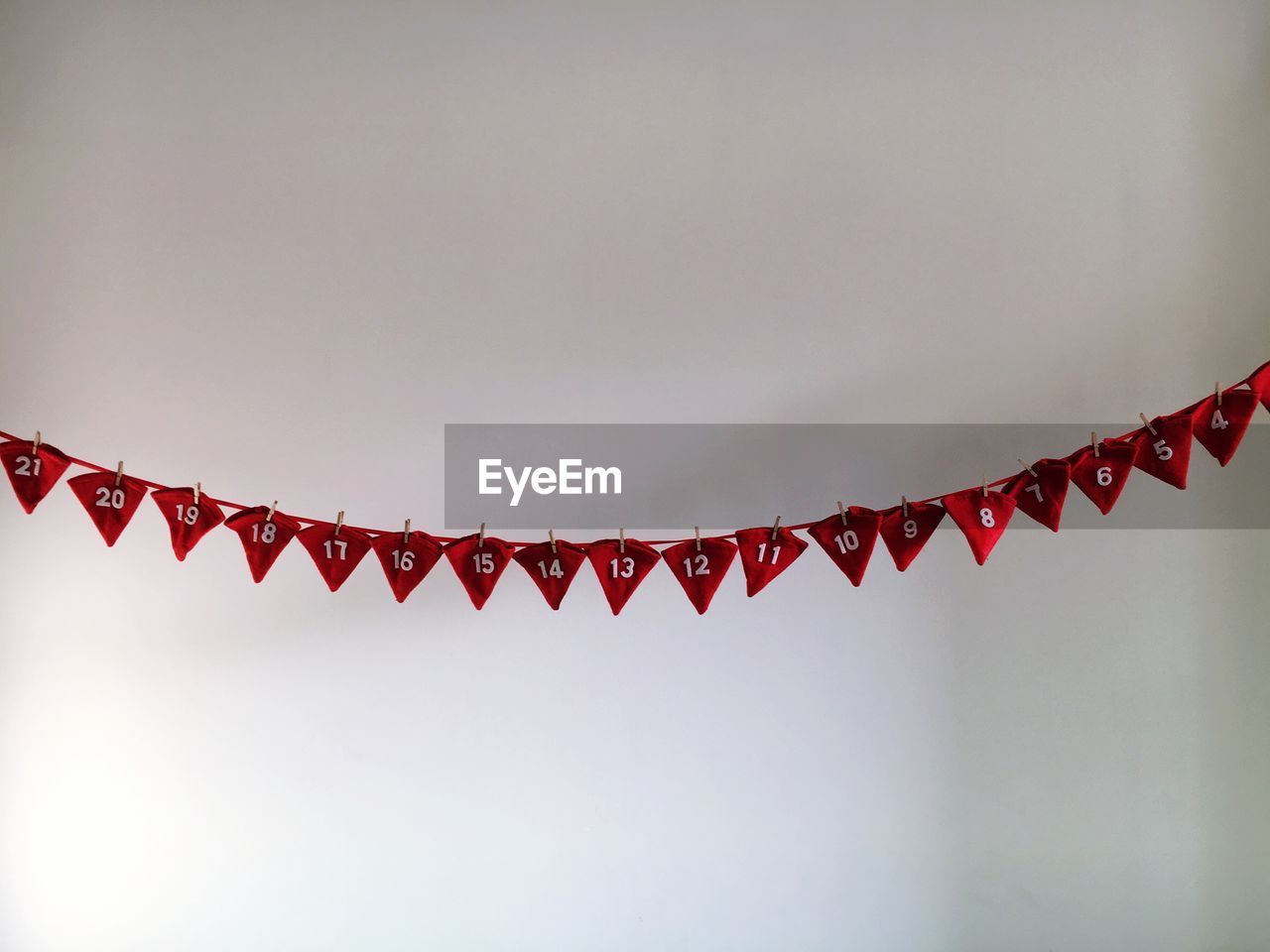 Santa hats with numbers hanging from rope against wall
