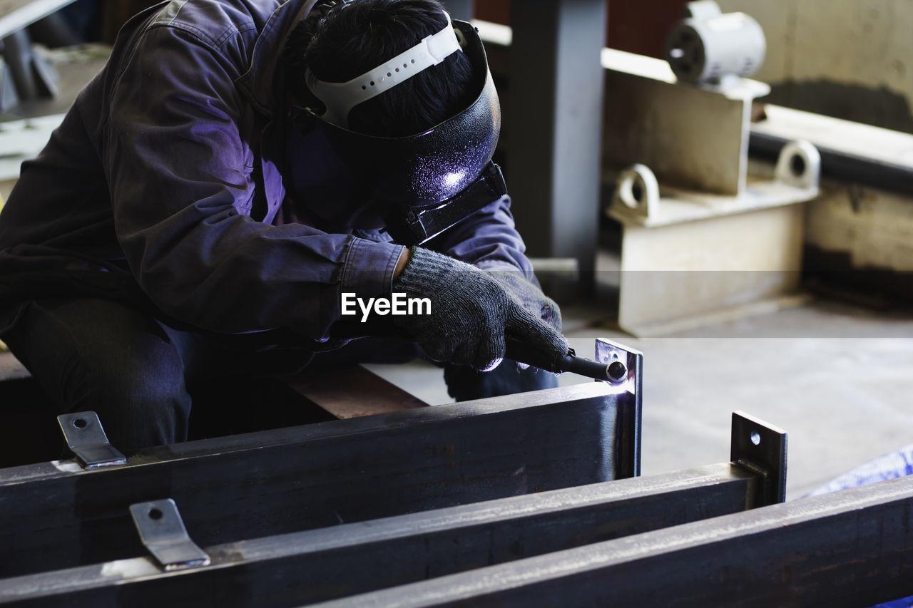 MAN WORKING ON METAL GRATE IN KITCHEN