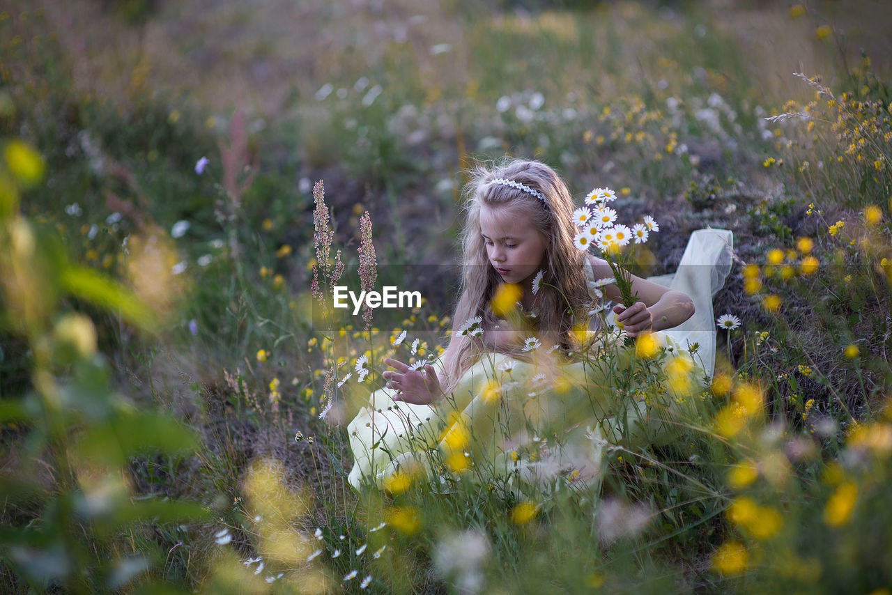 Full Length Of Girl With Yellow Flowers On Field