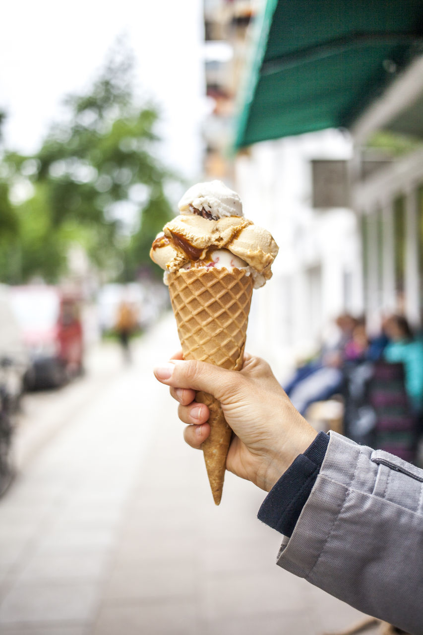 Cropped Image Of Hand Holding Ice Cream Cone On Street