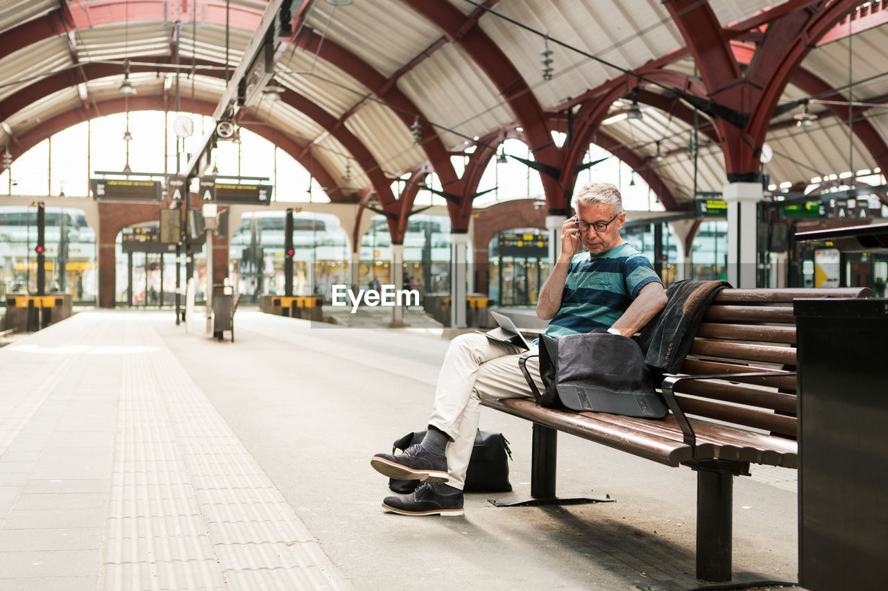 full length, sitting, seat, one person, real people, bench, lifestyles, day, architecture, indoors, leisure activity, rail transportation, transportation, public transportation, chair, adult, men, casual clothing, waiting