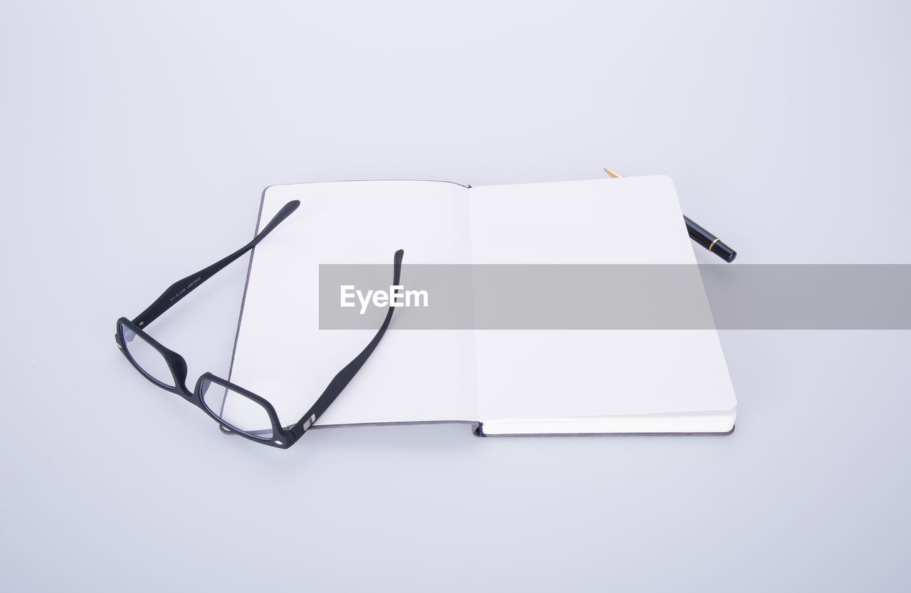 studio shot, white background, copy space, still life, indoors, no people, paper, eyeglasses, white color, close-up, cut out, blank, high angle view, glasses, pen, simplicity, art and craft, writing instrument, communication, two objects, personal accessory