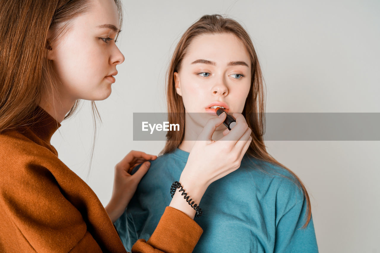 Close-Up Of Woman Applying Lipstick On Beautiful Young Friend Over White Background