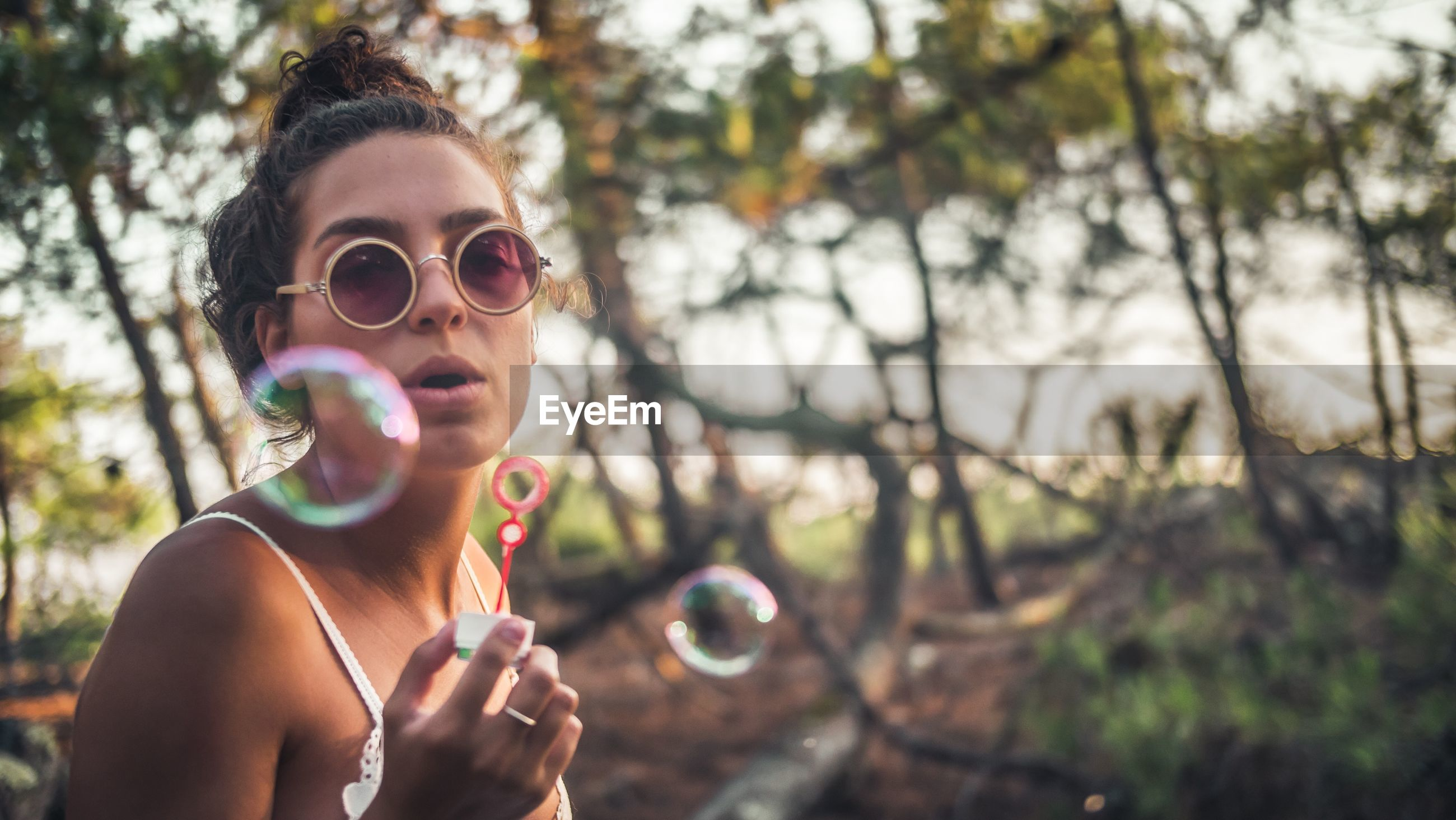 Young woman blowing bubbles at park