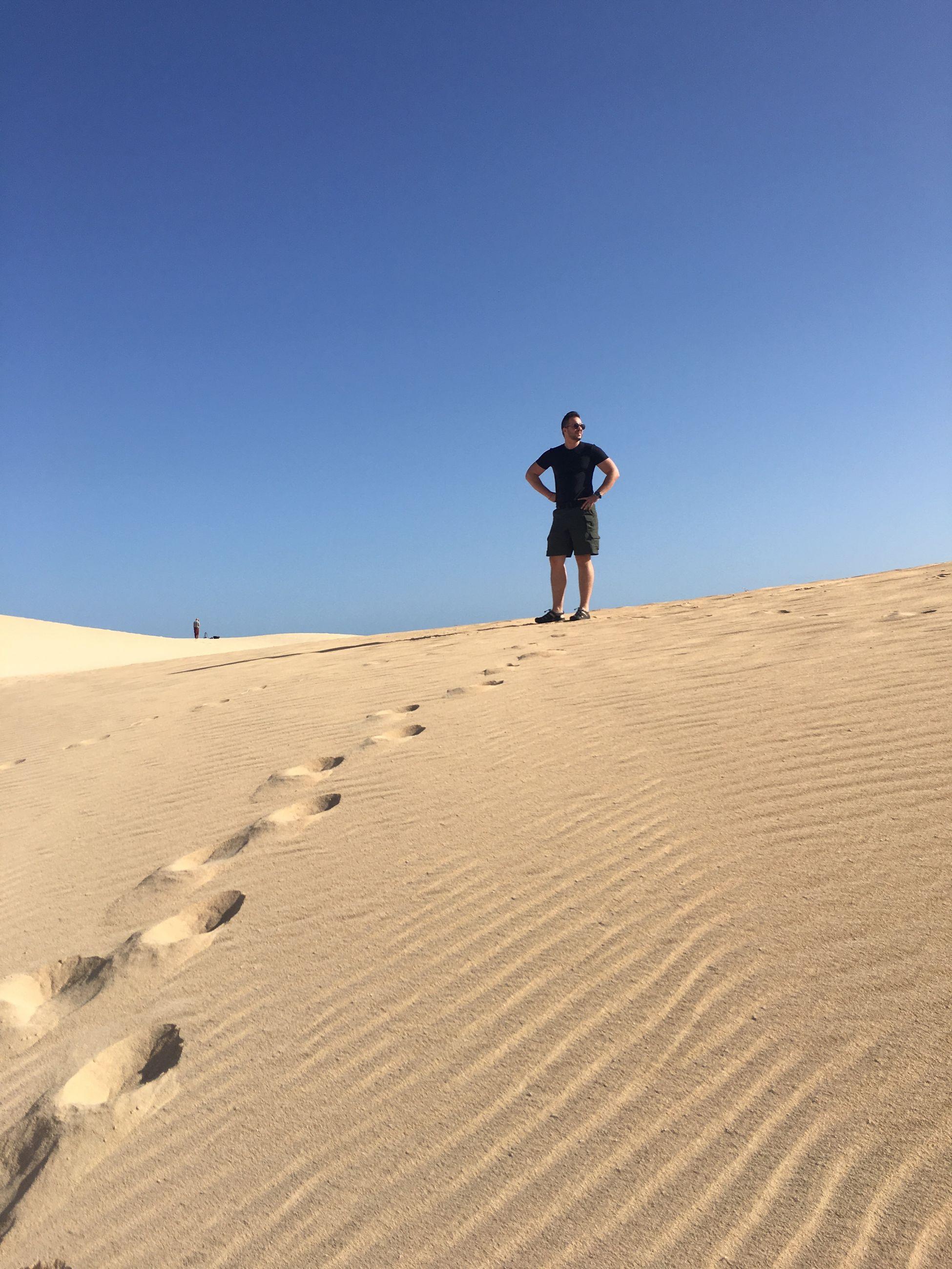 Full length of man standing at desert against clear blue sky