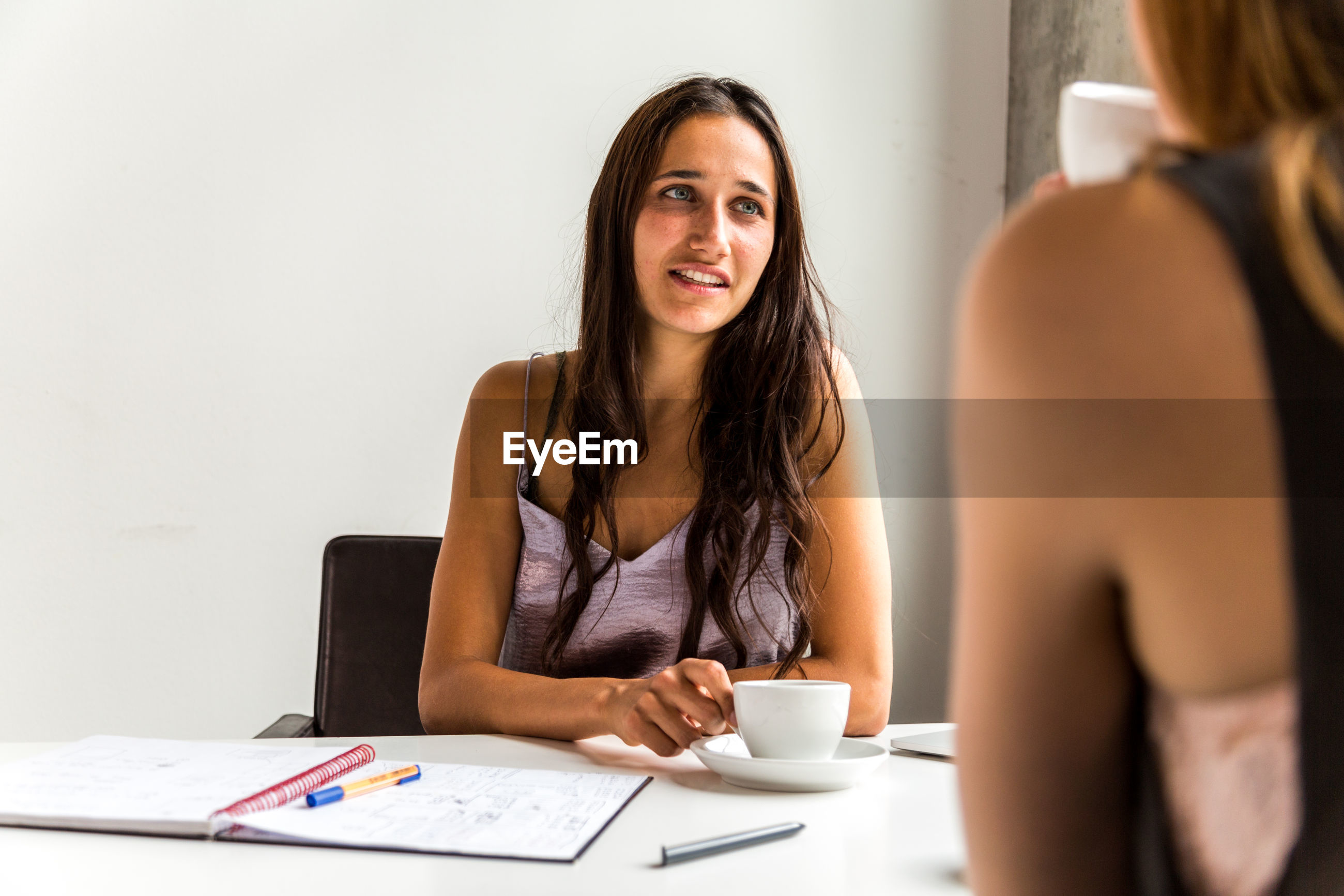 Businesswoman having coffee while discussing with female colleague in office