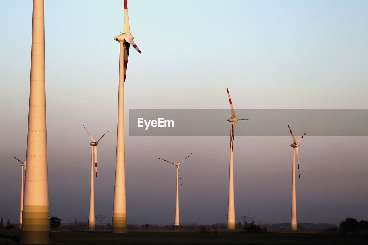 sky, turbine, wind turbine, renewable energy, wind power, alternative energy, environmental conservation, fuel and power generation, sunset, environment, nature, no people, technology, outdoors, clear sky, low angle view, air vehicle, flying, architecture, vertebrate