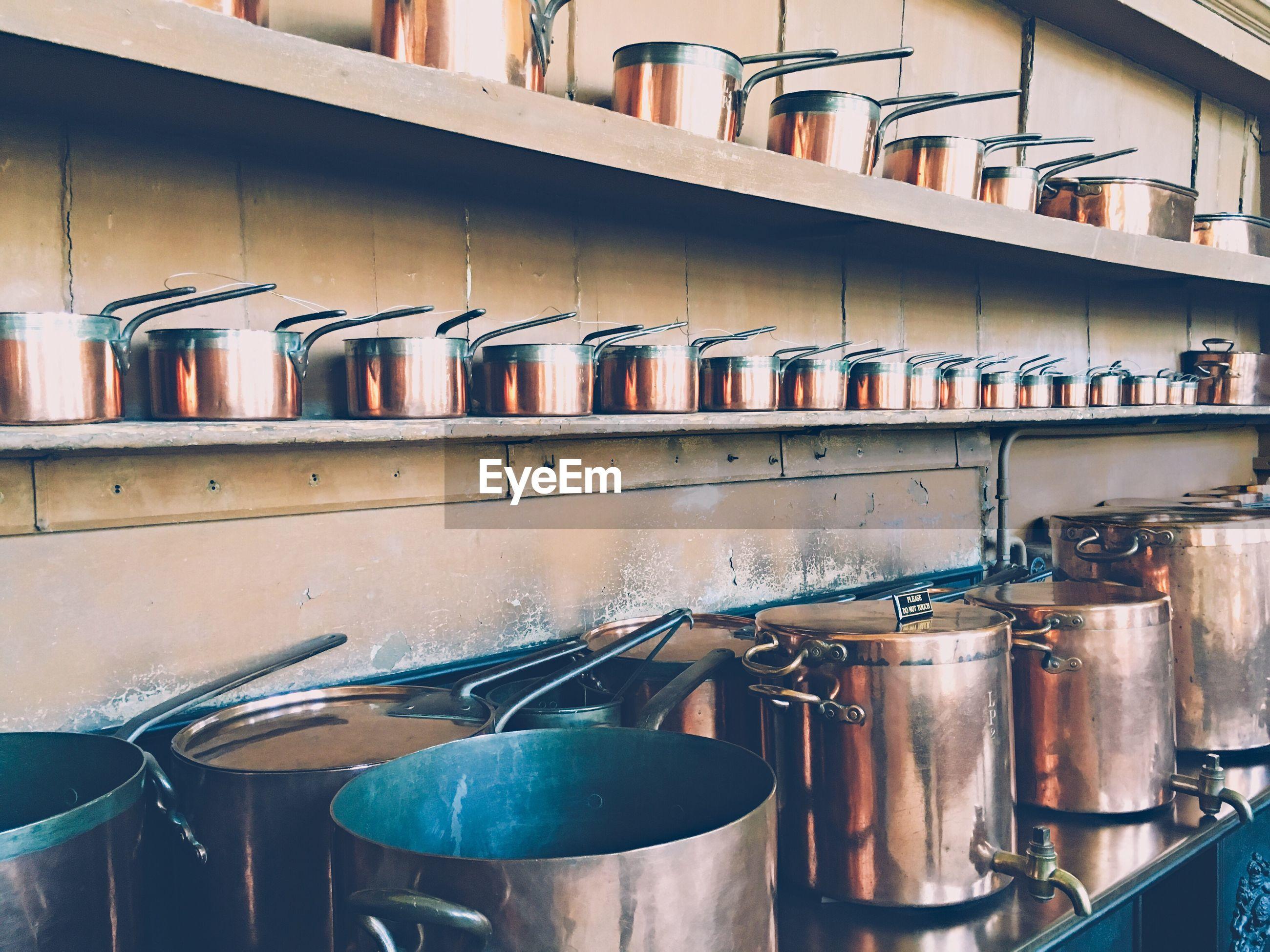 Copper utensils arranged on shelf in kitchen