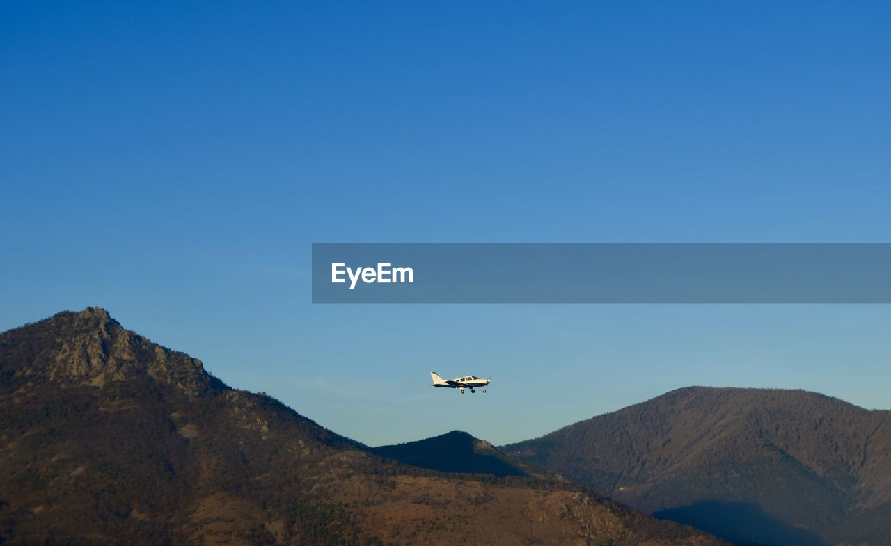 Low angle view of airplane flying over mountains against blue sky