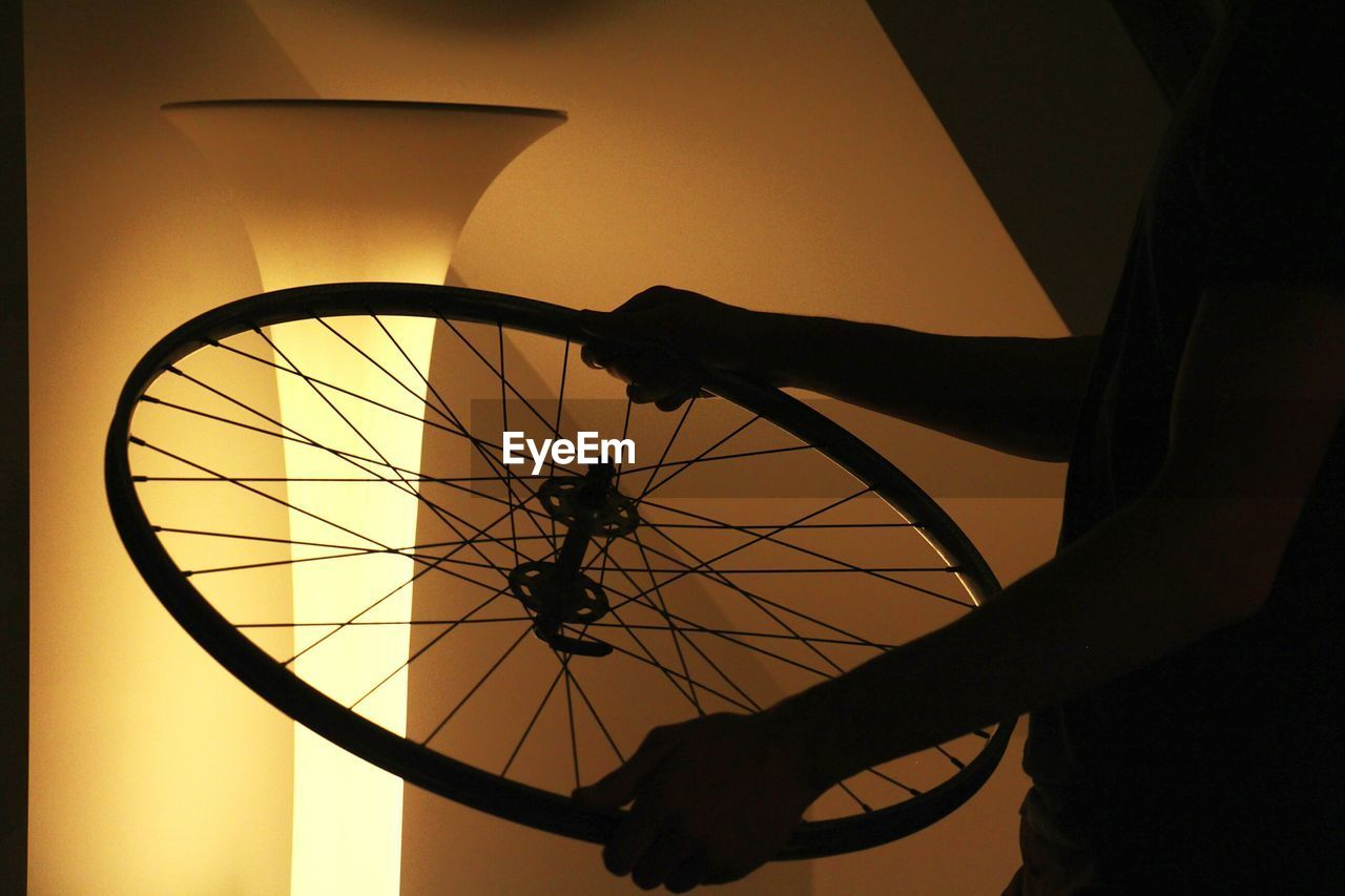 Midsection Of Man Holding Bicycle Spoke By Illuminated Lamp Shade