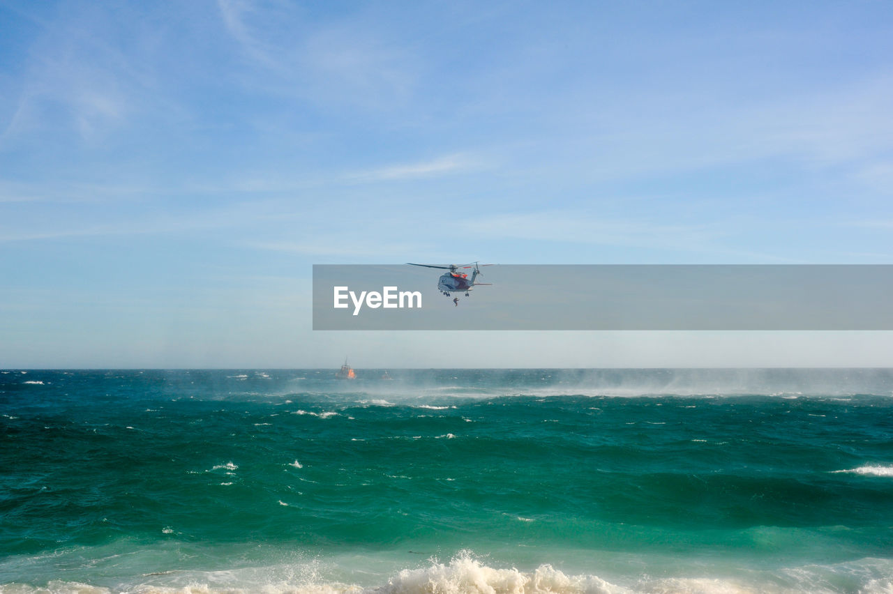 Rescue Helicopter Flying Over Sea Against Sky