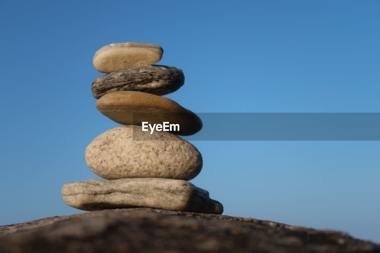 solid, balance, stack, sky, rock, stone - object, zen-like, rock - object, blue, clear sky, no people, stone, low angle view, nature, pebble, close-up, day, tranquility, textured, outdoors