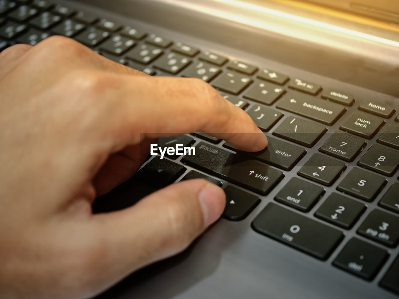 CROPPED IMAGE OF PERSON USING LAPTOP