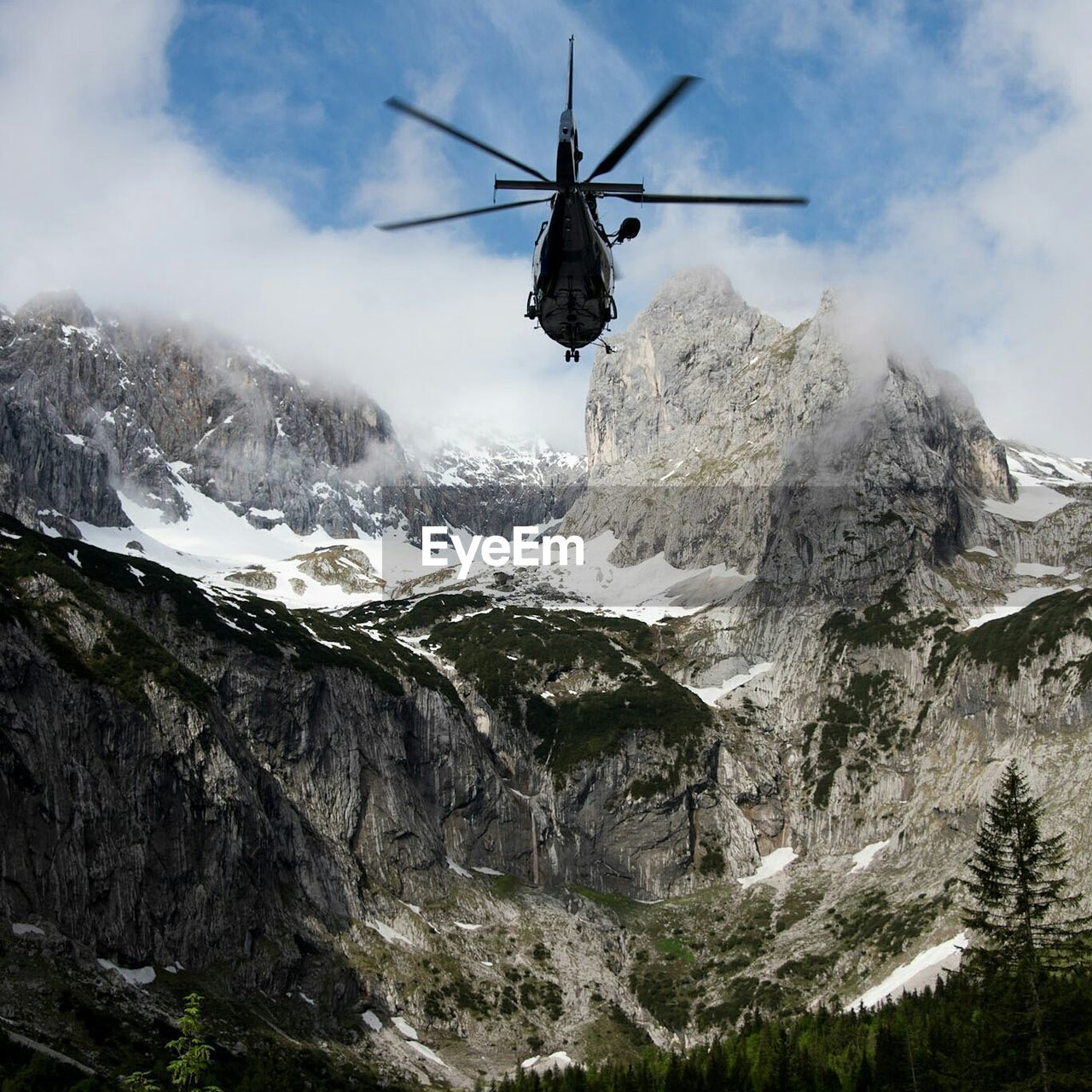 Low Angle View Of Helicopter Over Snowcapped Mountains Against Sky