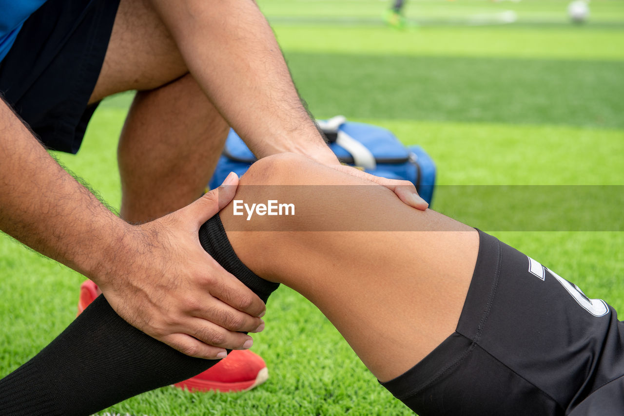 Low Section Of Male Physical Therapist Rubbing Soccer Player Knee On Field