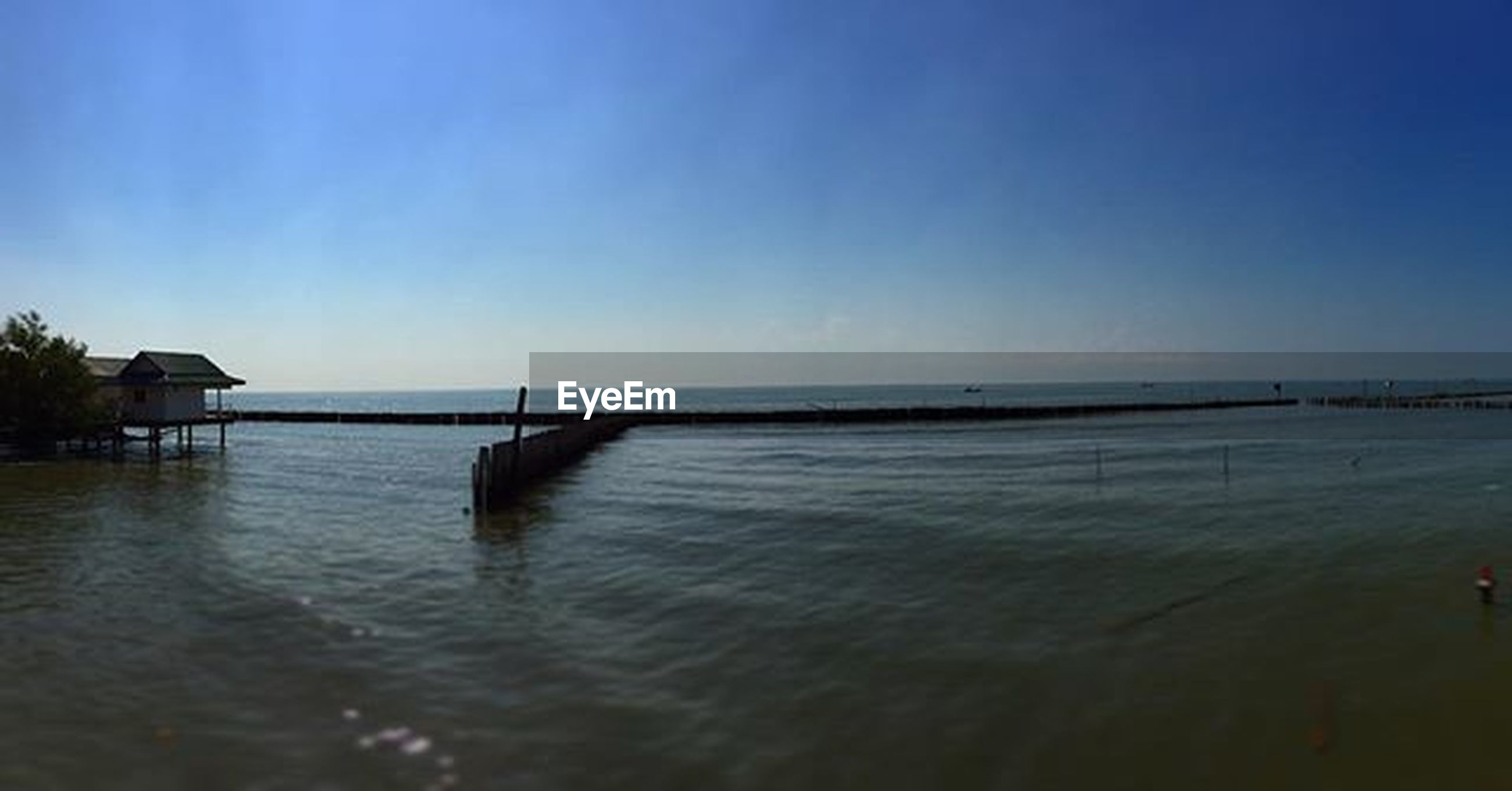 water, sea, clear sky, tranquil scene, copy space, horizon over water, tranquility, scenics, blue, beauty in nature, nature, idyllic, waterfront, rippled, calm, pier, reflection, sky, beach, ocean
