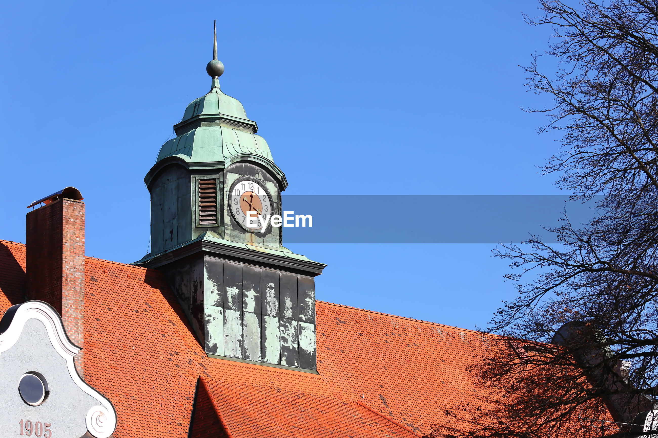 LOW ANGLE VIEW OF CLOCK TOWER AND BUILDINGS AGAINST CLEAR BLUE SKY