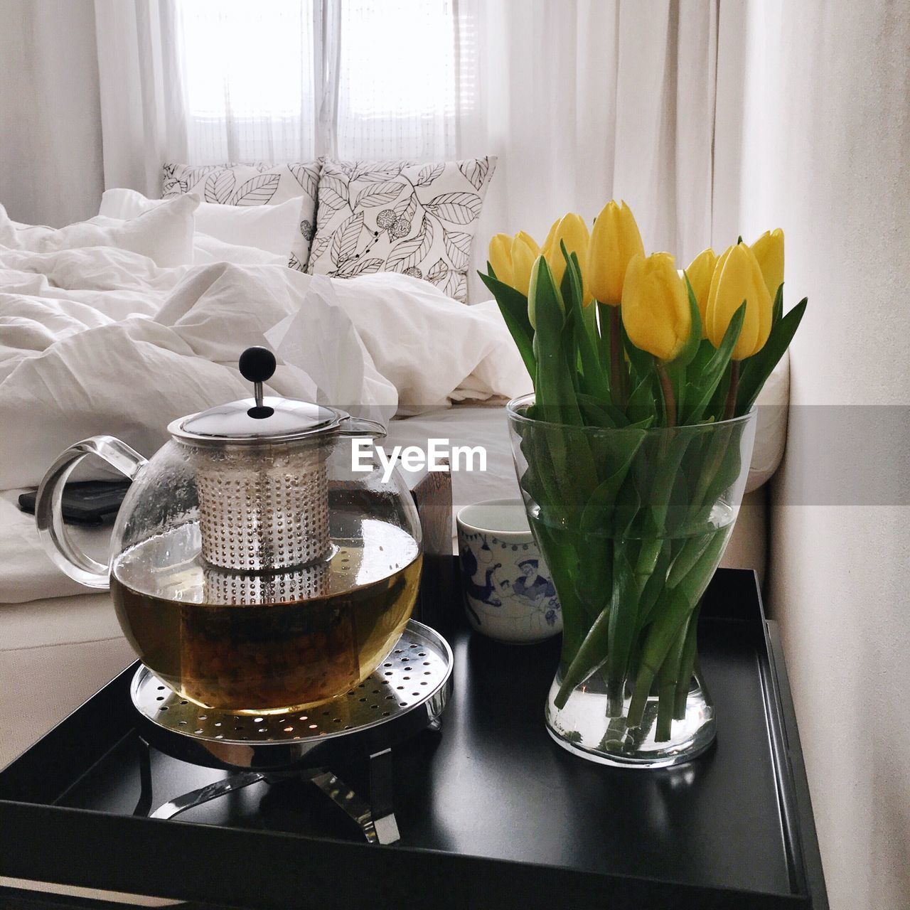 Close-Up Of Tulips In Vase By Herbal Tea Kettle On Table At Home