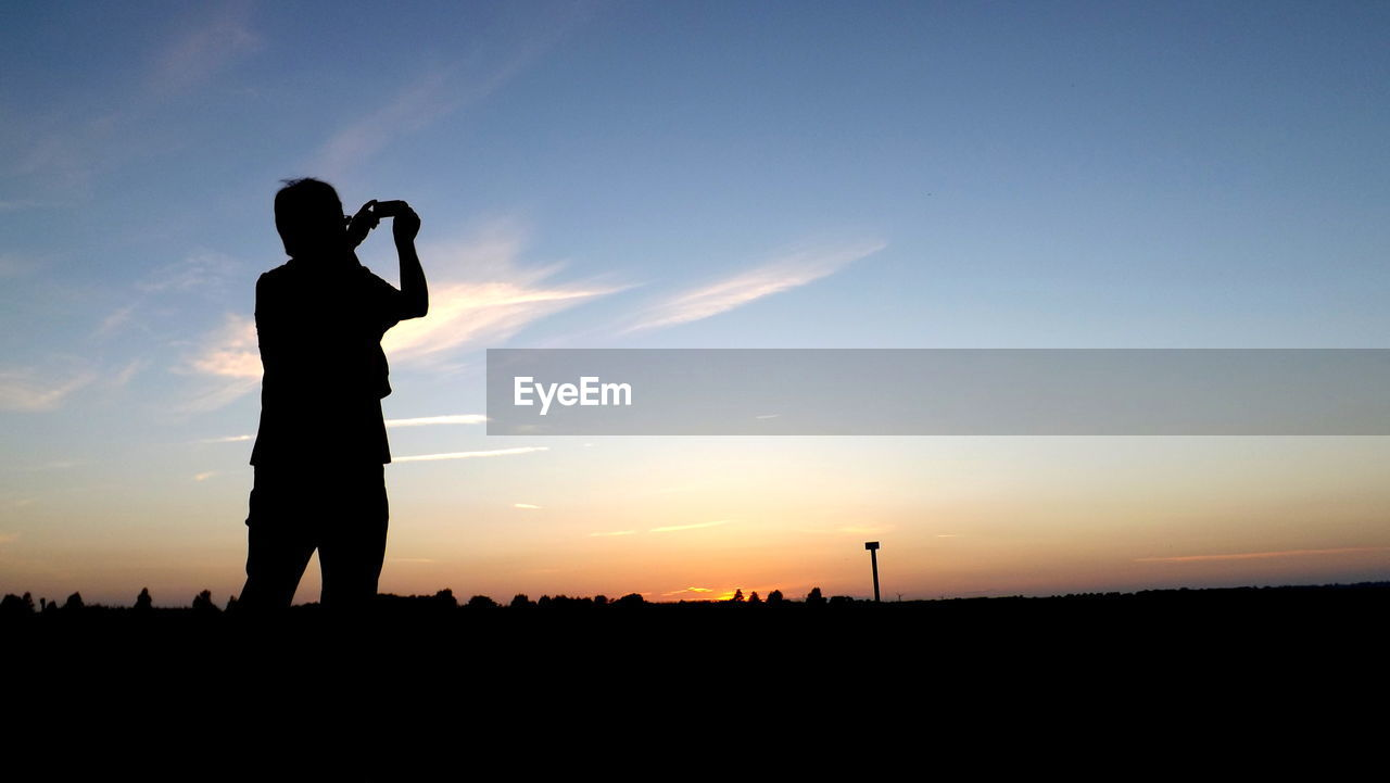 Silhouette of man taking pictures of sunset