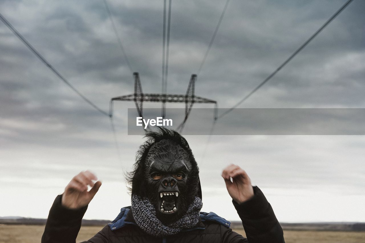 Man wearing gorilla mask against cloudy sky