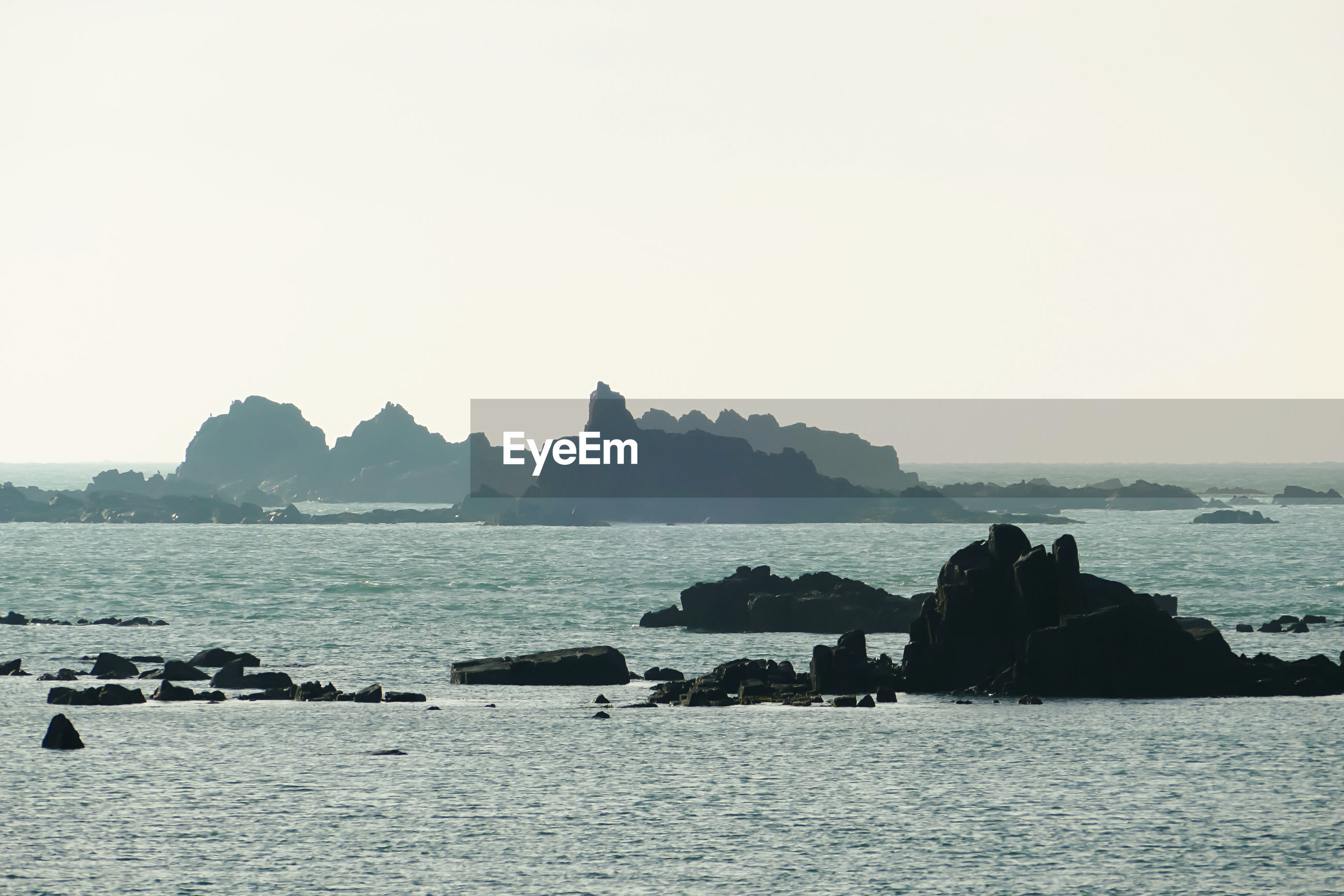 SCENIC VIEW OF ROCKS ON SEA AGAINST CLEAR SKY