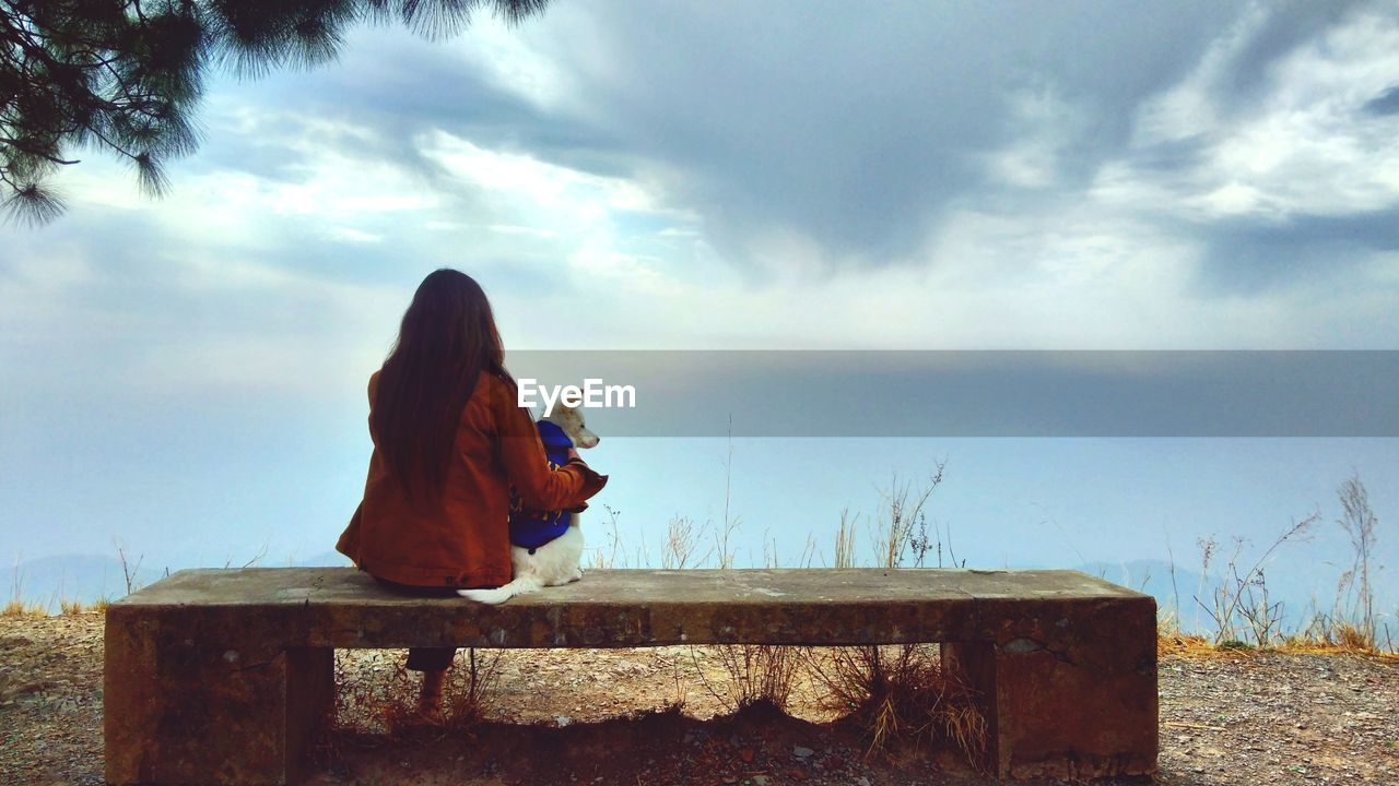 Rear view of woman sitting on a bech with dog against sky
