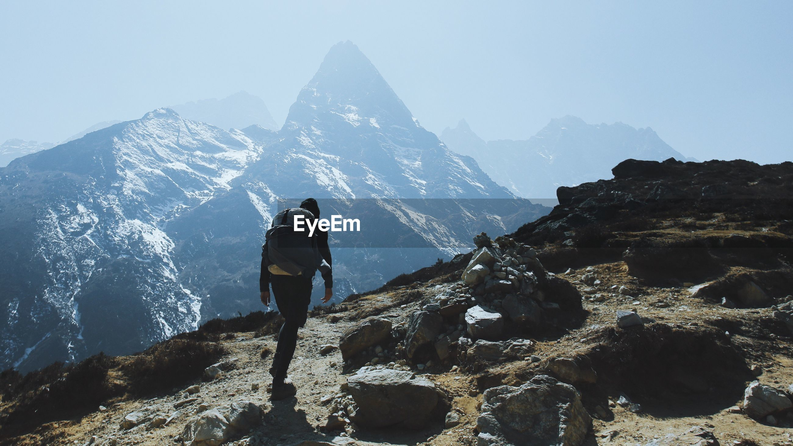 MAN STANDING ON ROCKY MOUNTAIN