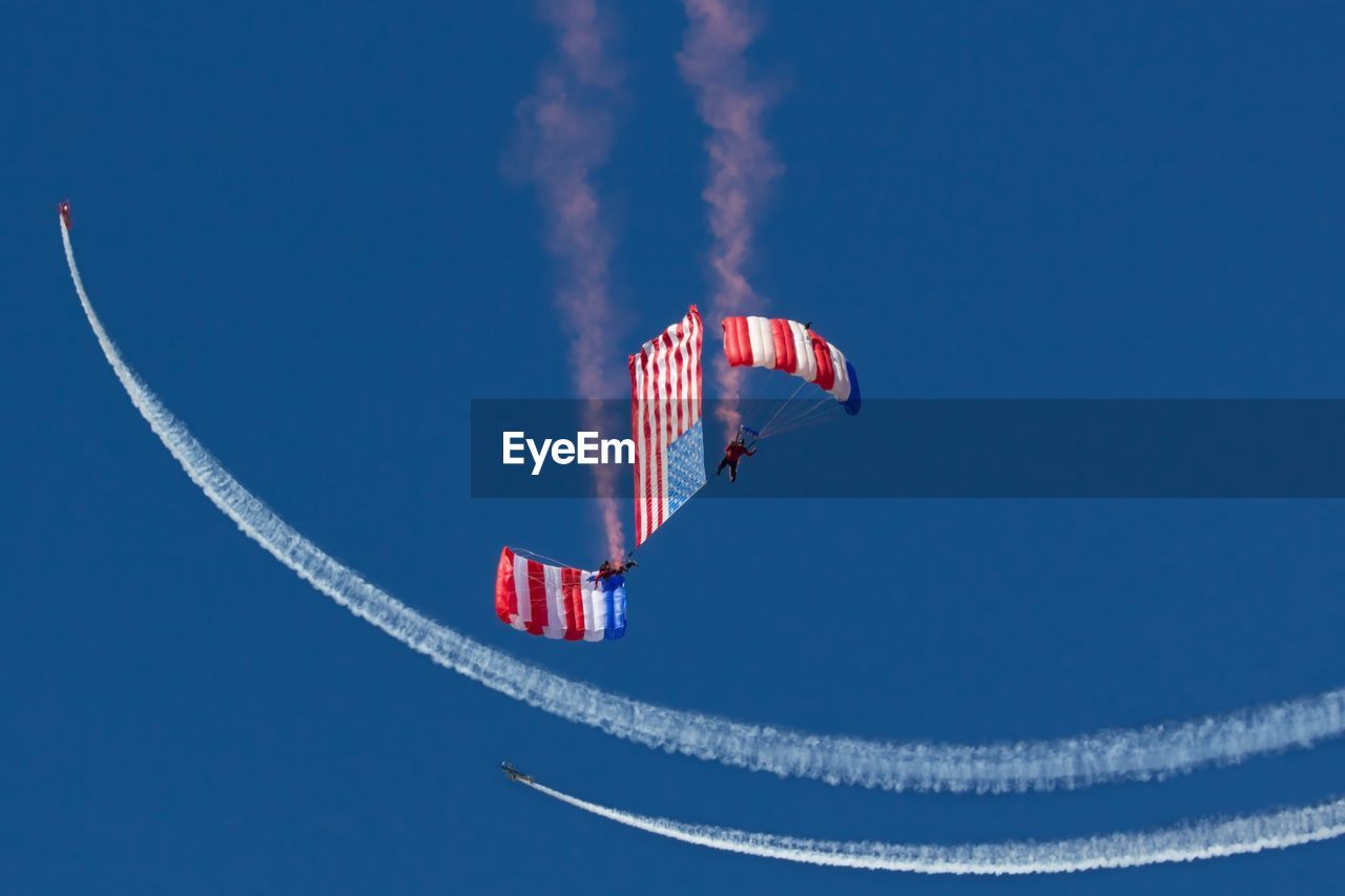 Low Angle View Of Men Paragliding With American Flag In Clear Blue Sky